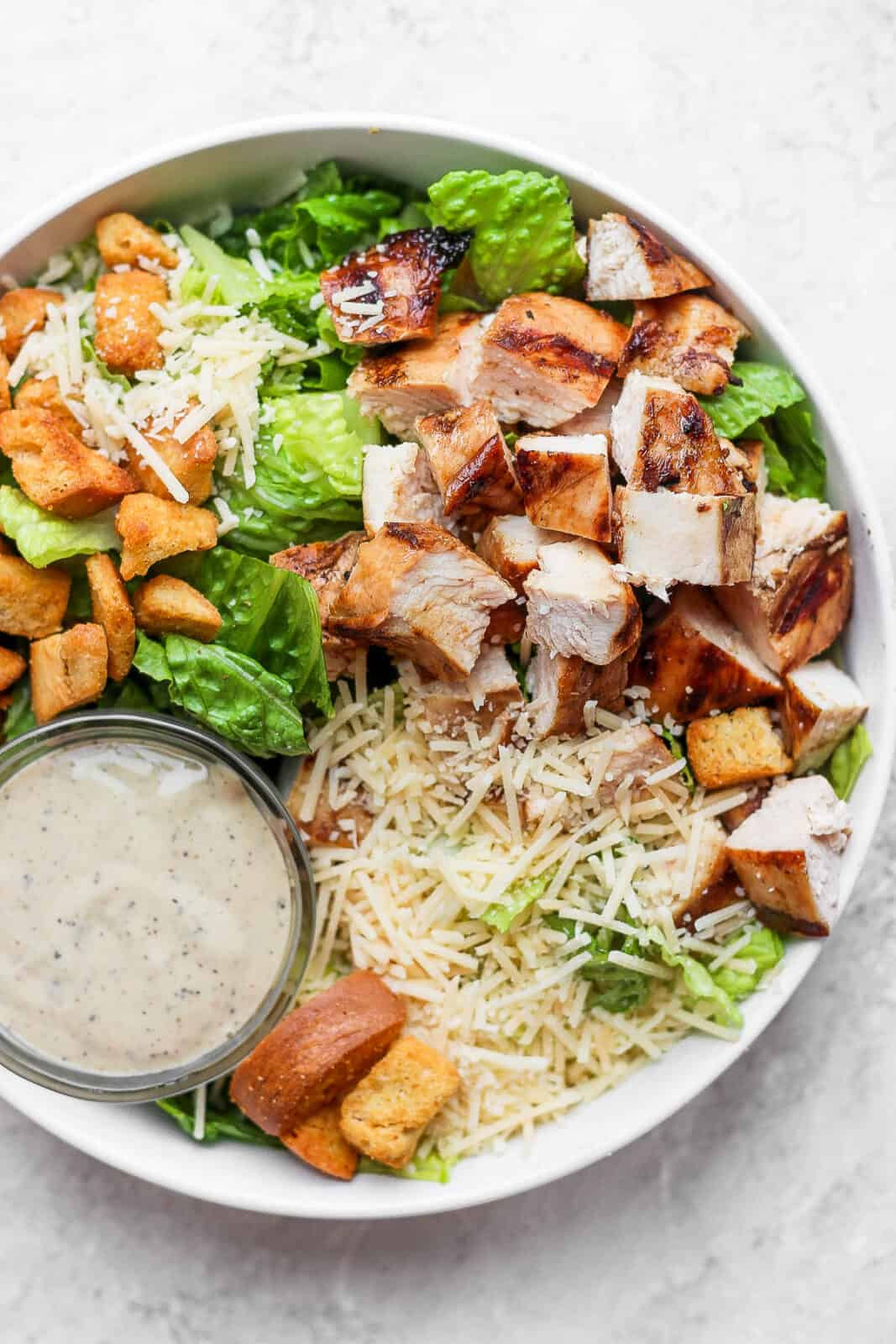 Grilled chicken caesar salad with a small dish of dressing.