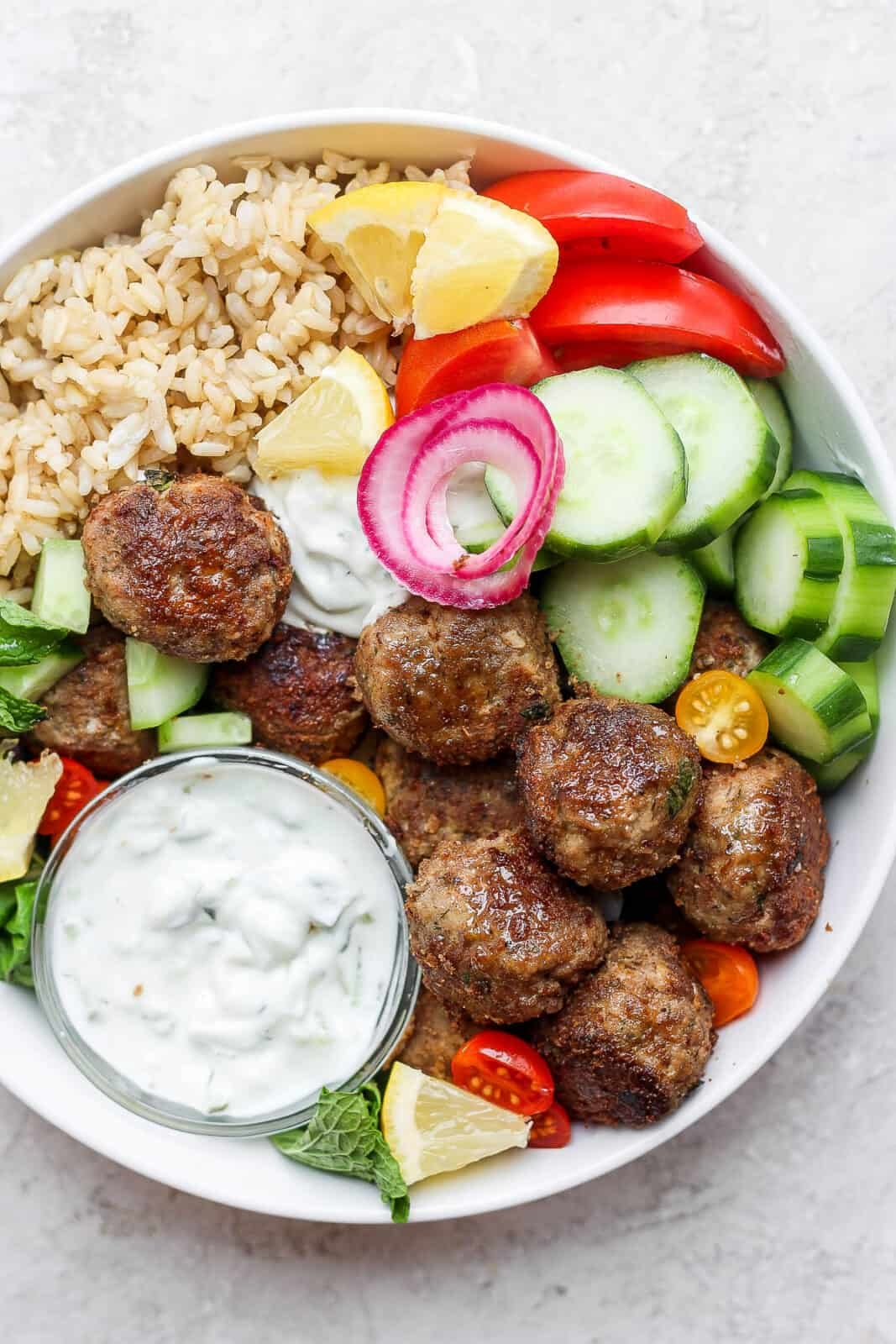A gyro bowl with lamb meatballs, tzatziki sauce, tomatoes and cucumbers.