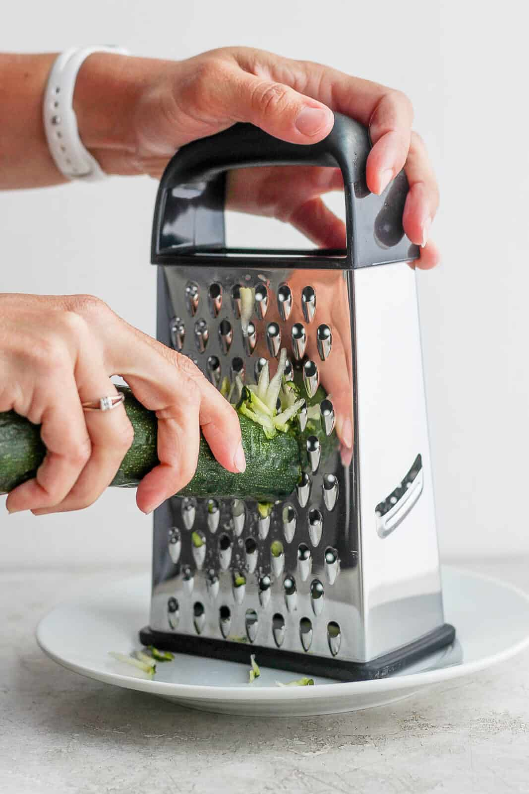 Someone grating zucchini with a box grater.