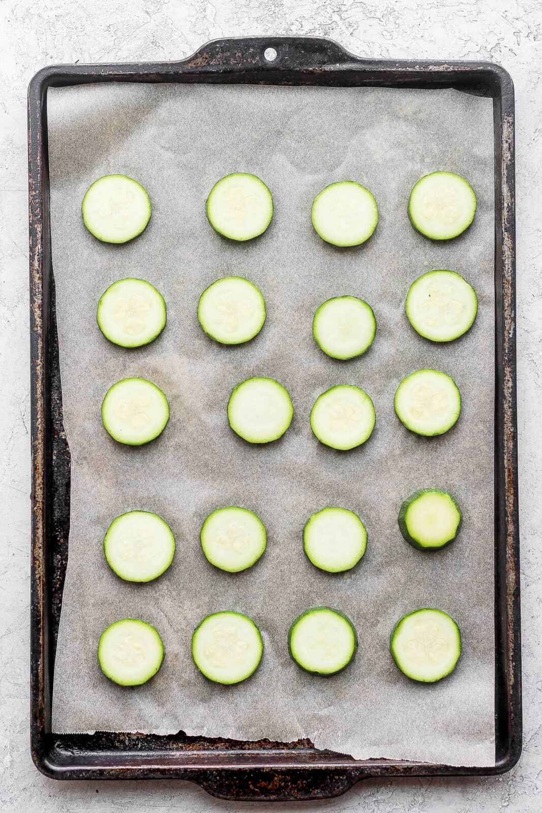 Blanches slices of zucchini on a parchment-lined baking sheet.