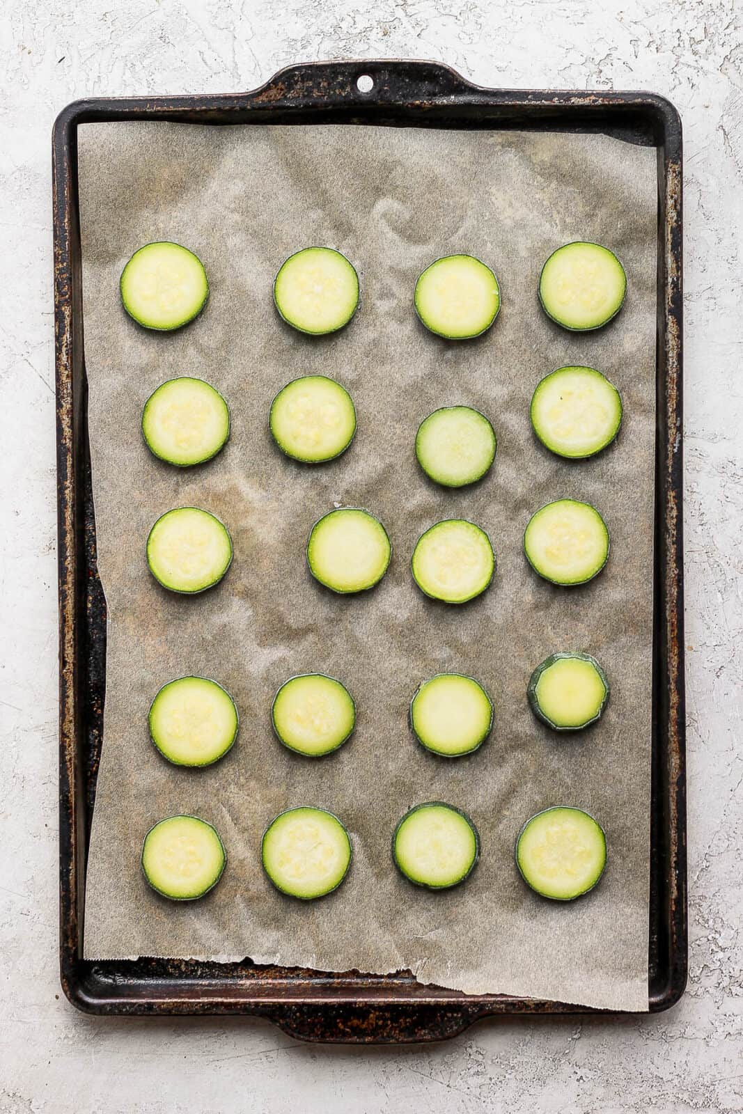 Frozen slices of zucchini on a parchment linked baking sheet.