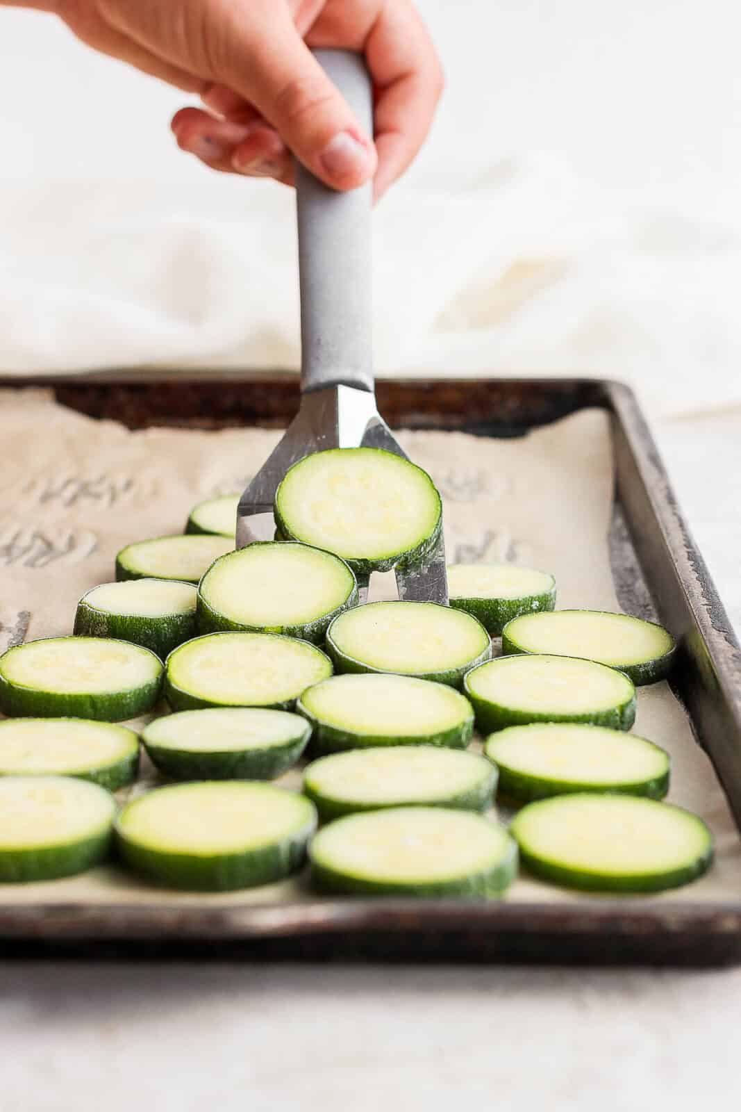Someone scooping up frozen zucchini slices with a spatula.