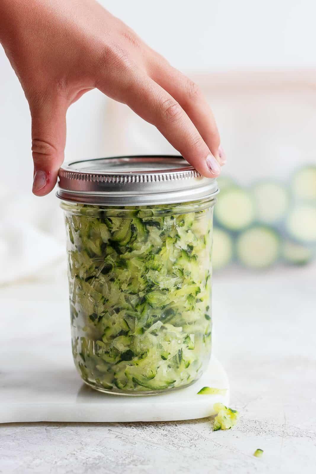 A mason jar of shredded zucchini.
