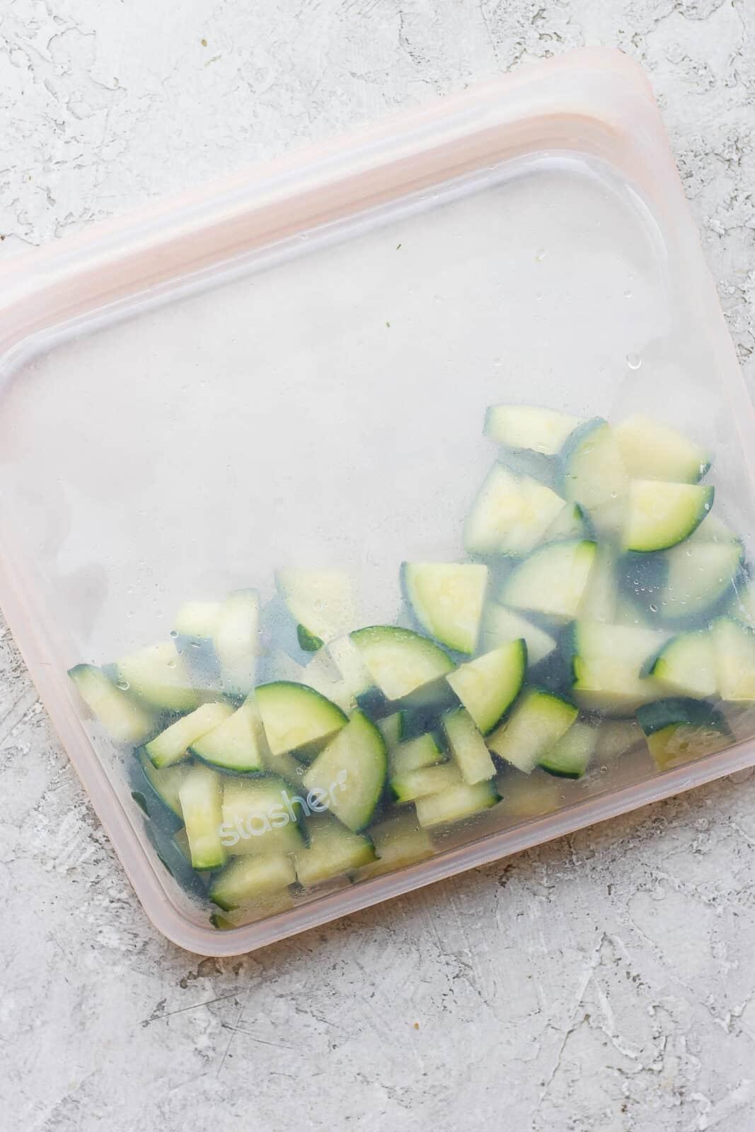 Frozen zucchini quarters in a silicone storage bag.