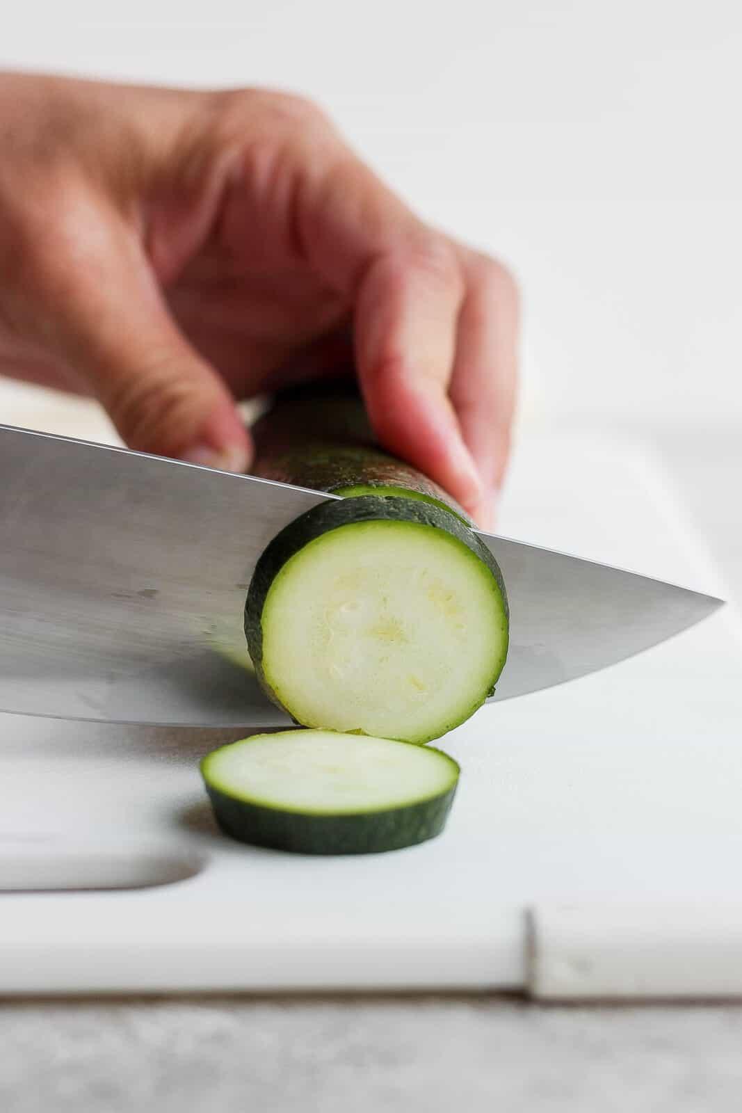 Someone slices a zucchini.