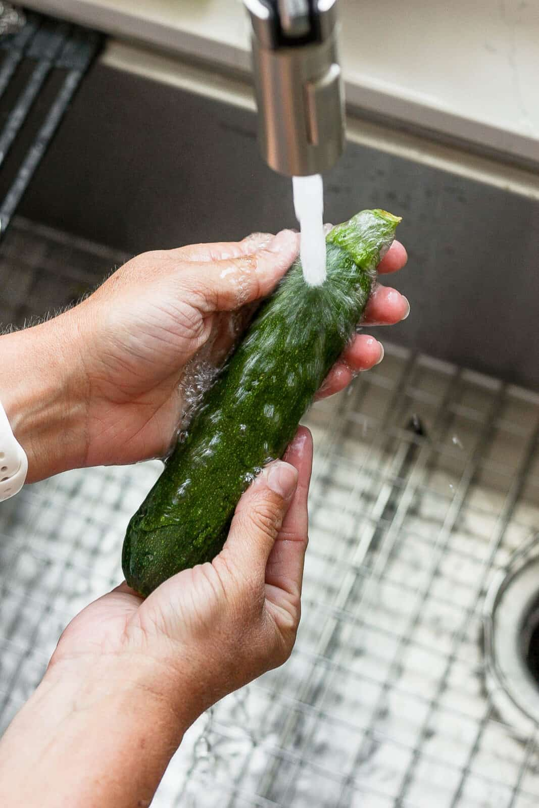 Someone washing off a zucchini in the sink.