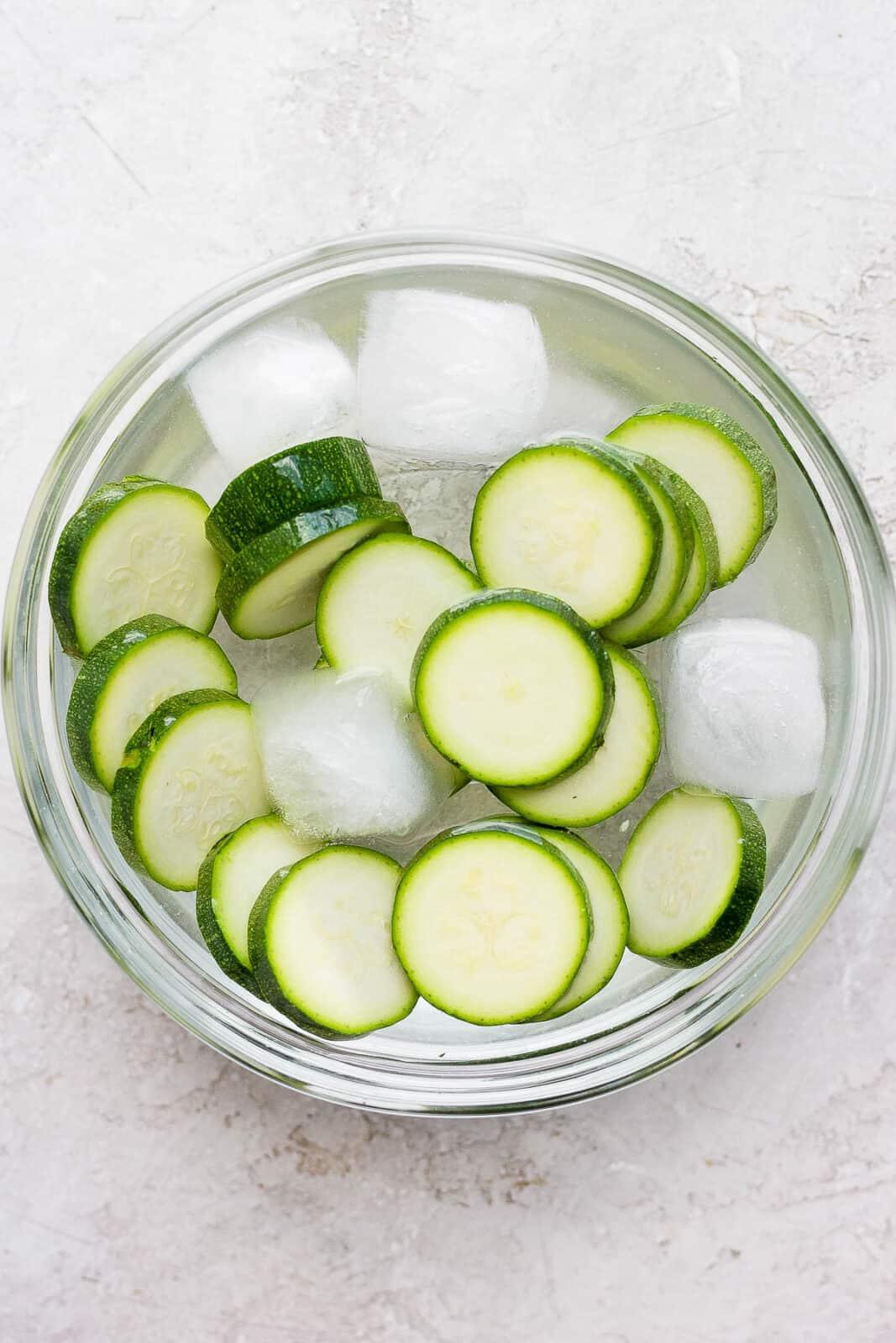 Zucchini slices in an ice bath.