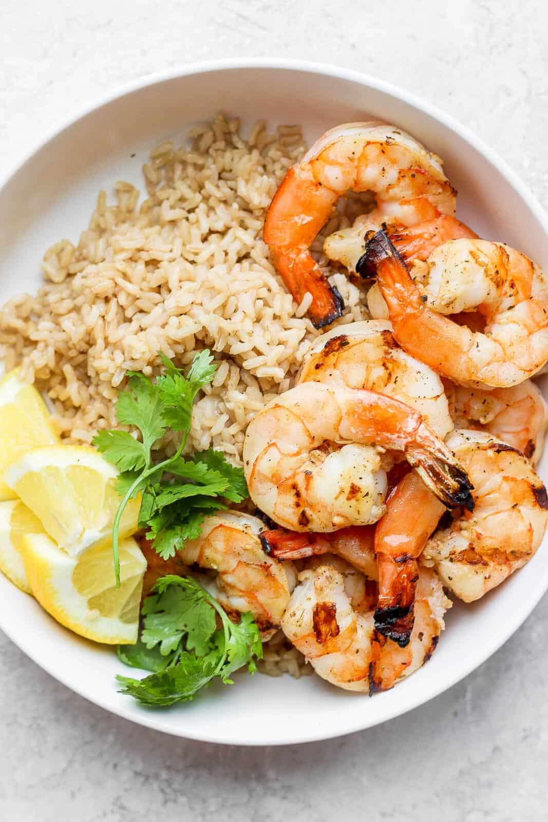 Grilled shrimp in a bowl with brown rice.