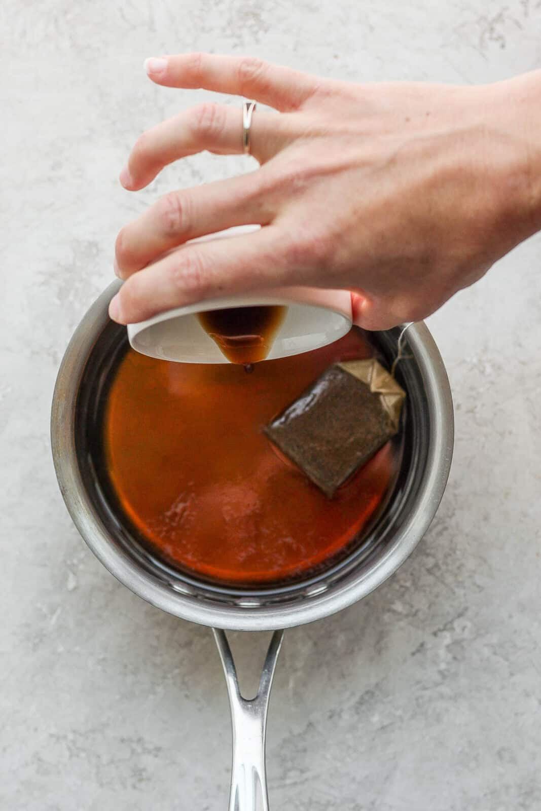 Adding maple syrup and vanilla to earl grey tea steeping in a small saucepan.