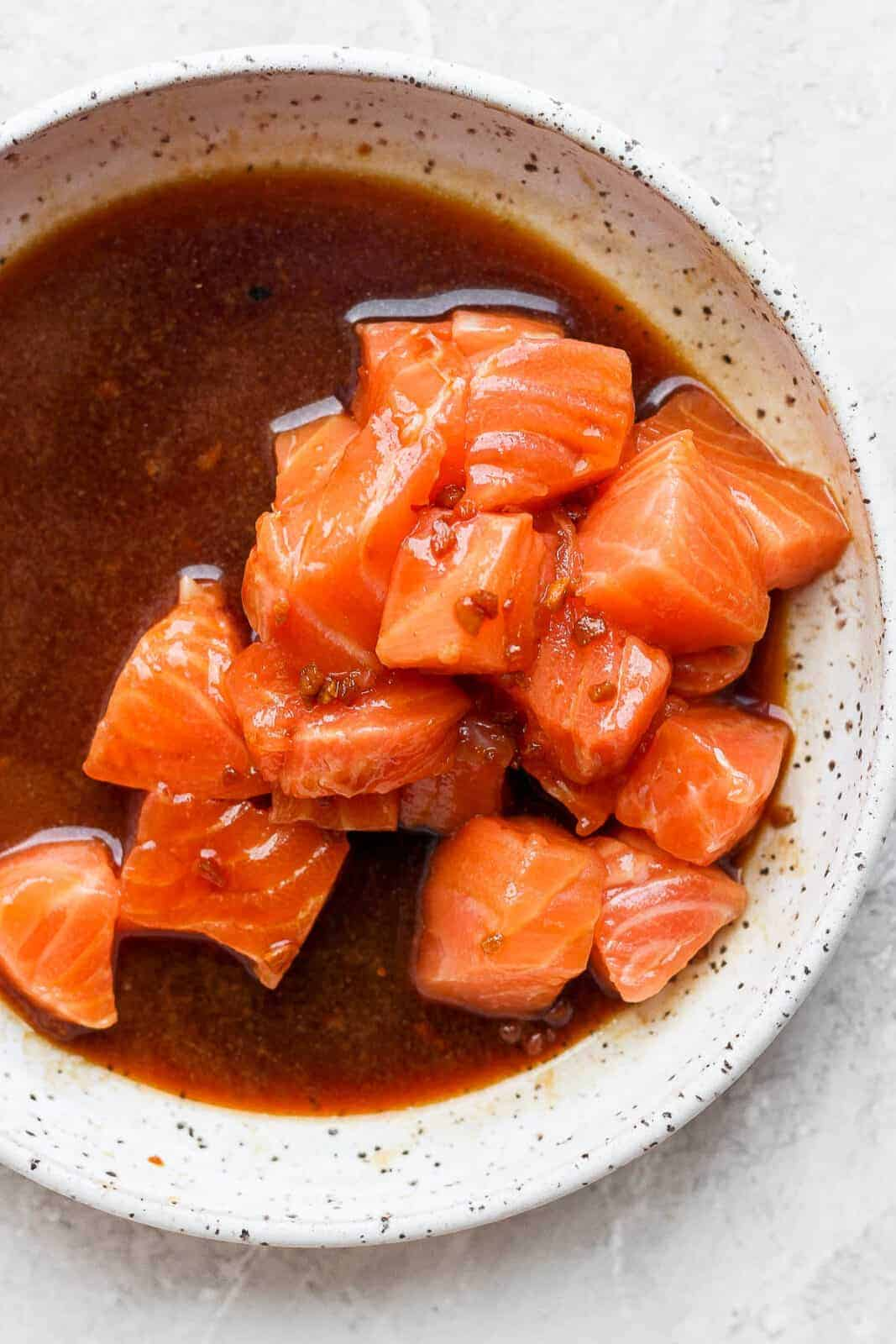 Cut up pieces of sushi grade salmon in a bowl with the poke sauce.
