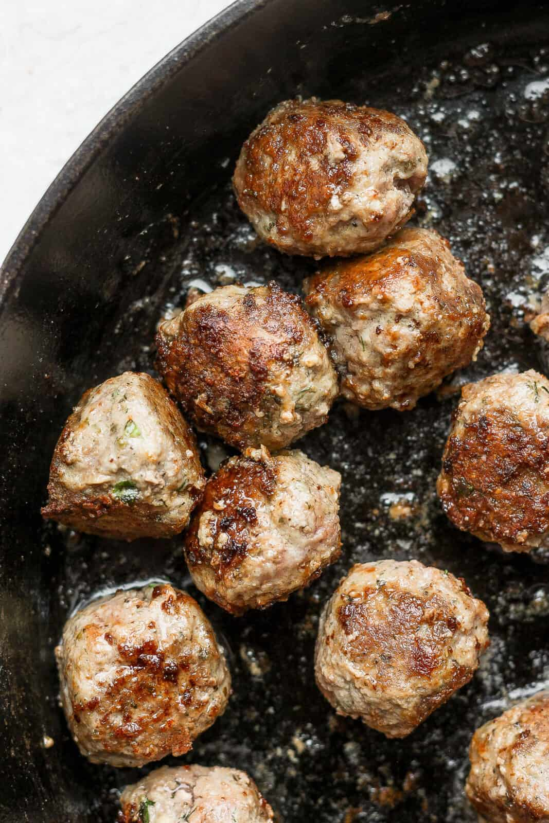 Lamb meatballs fried in a cast iron pan.