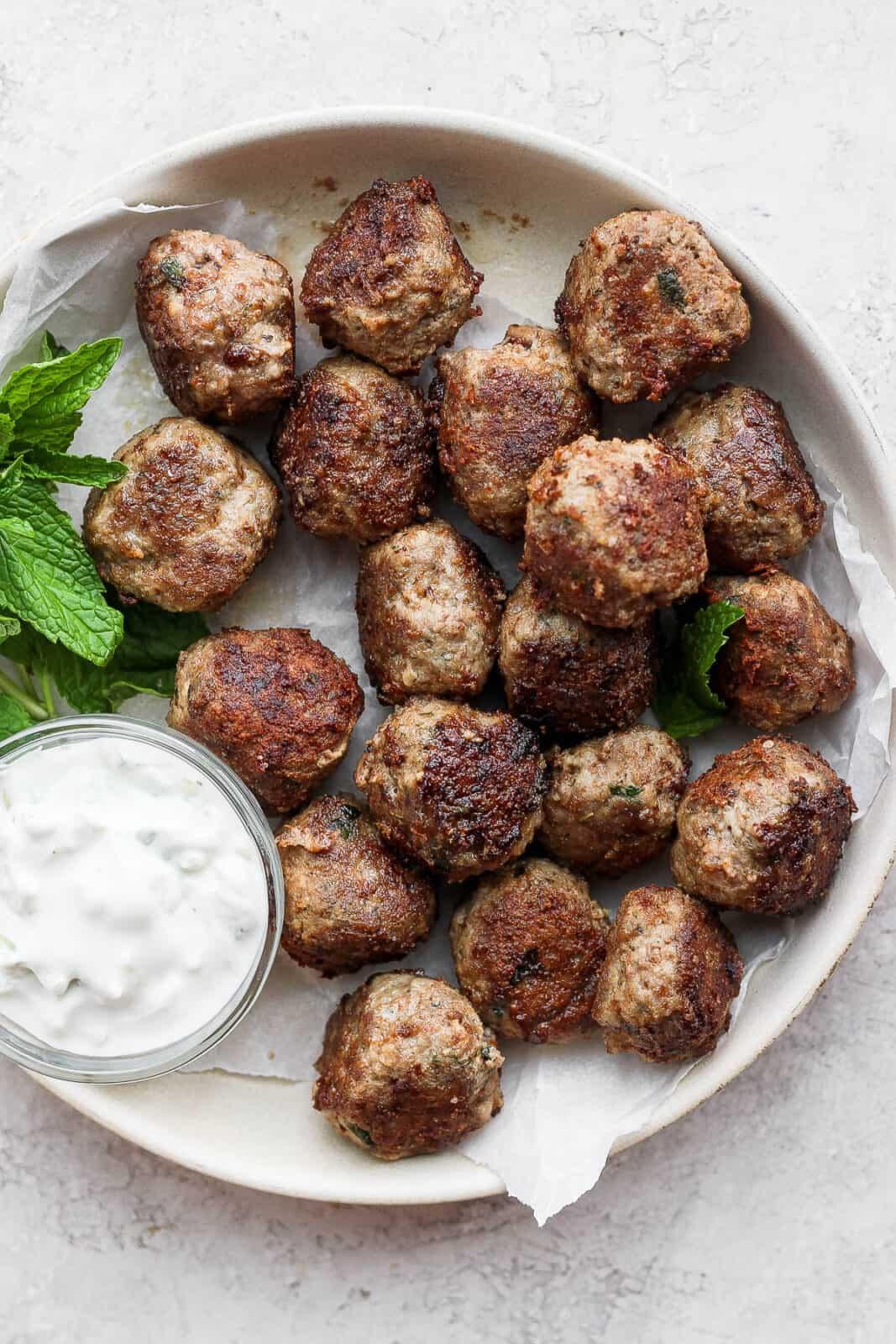 A shallow bowl of lamb meatballs with mint and tzatziki sauce.
