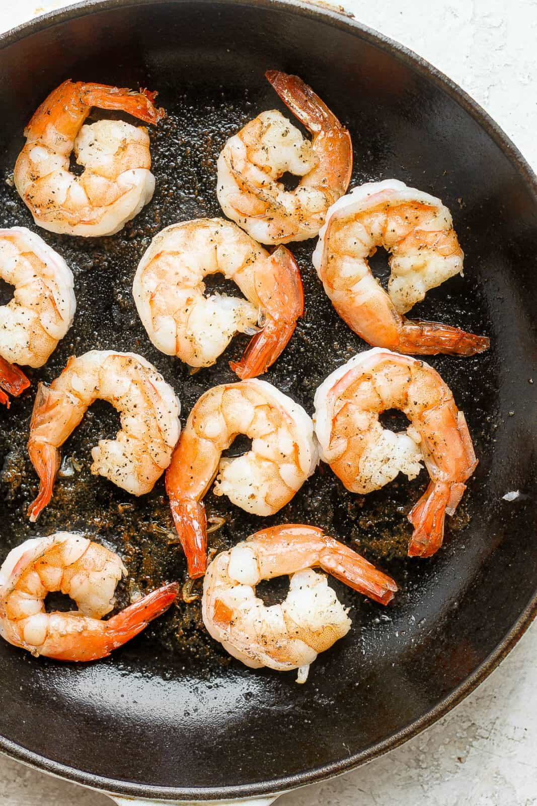 Pan fried shrimp in a cast iron pan.