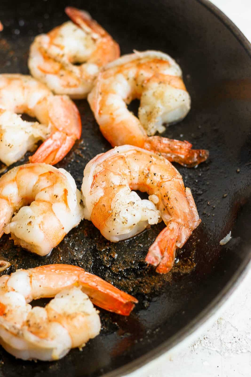 Shrimp being cooked in a cast iron skillet.