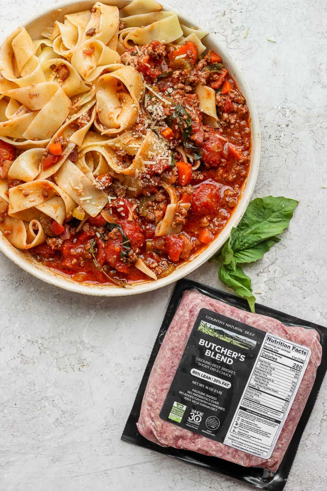 Bowl of pappardelle bolognese with a package of butcher's blend ground beef.