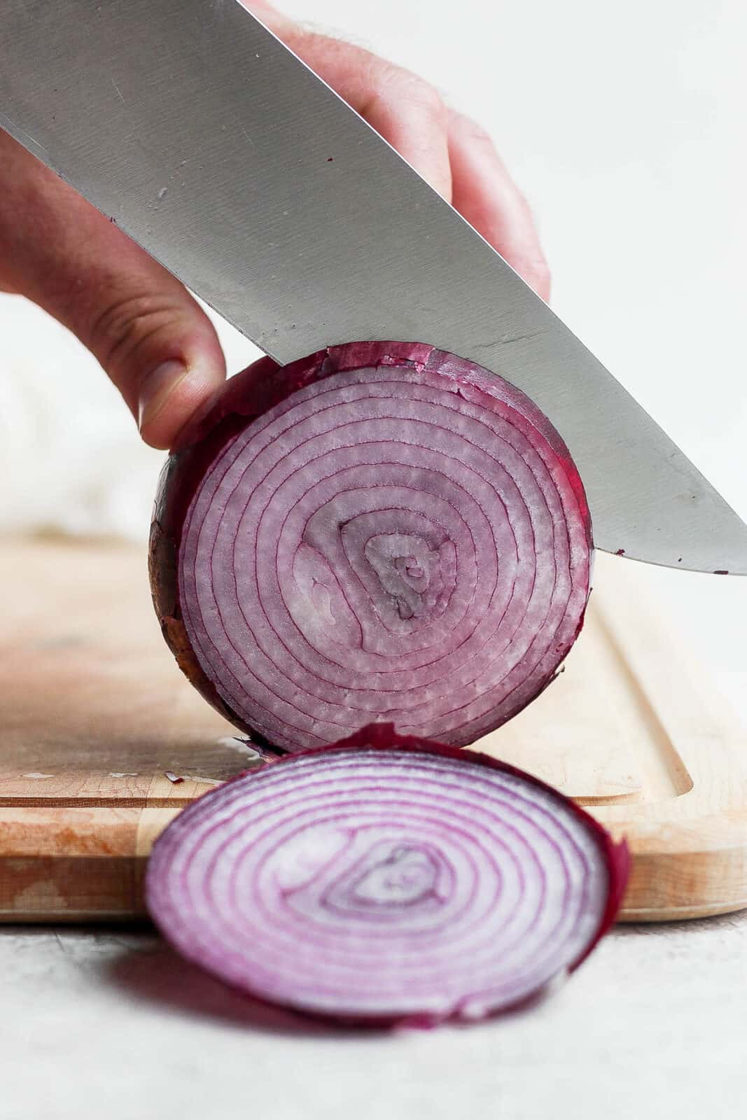 A red onion being sliced on a cutting board.