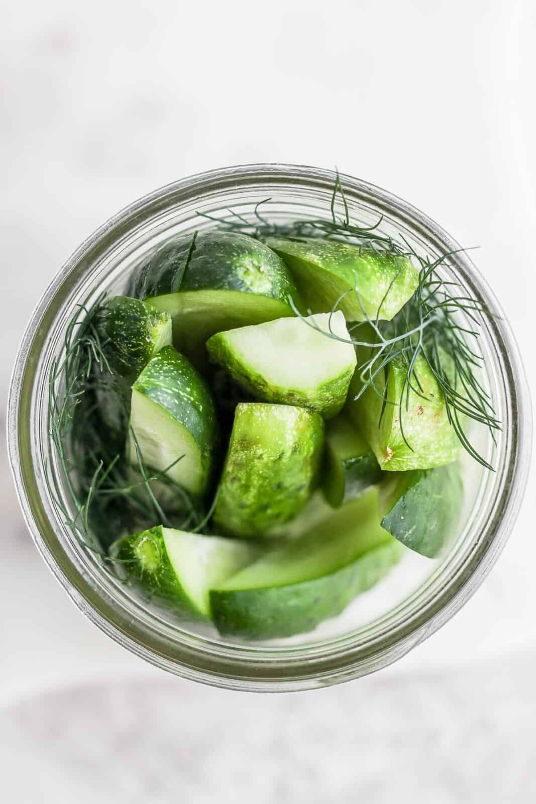 Top view of mason jar with sliced cucumbers and fresh dill inside.