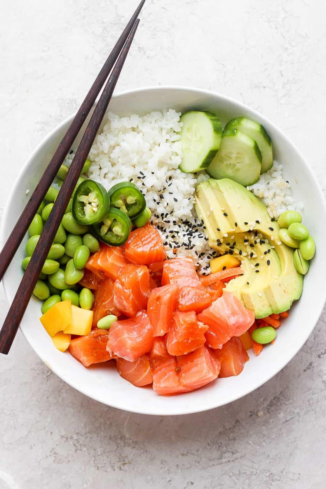 A salmon poke bowl with chopsticks.