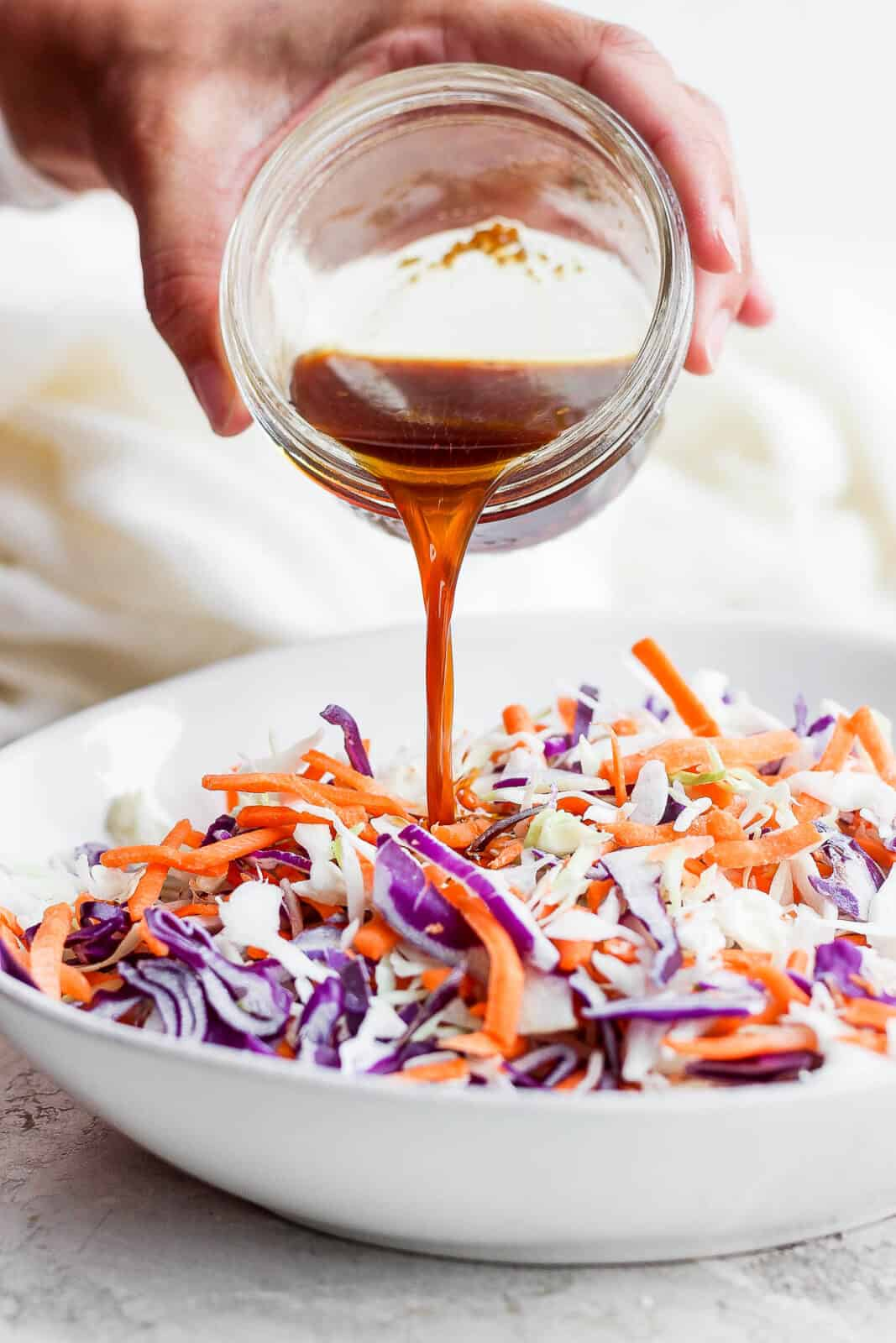The sauce being poured from a mason jar onto the slaw ingredients.