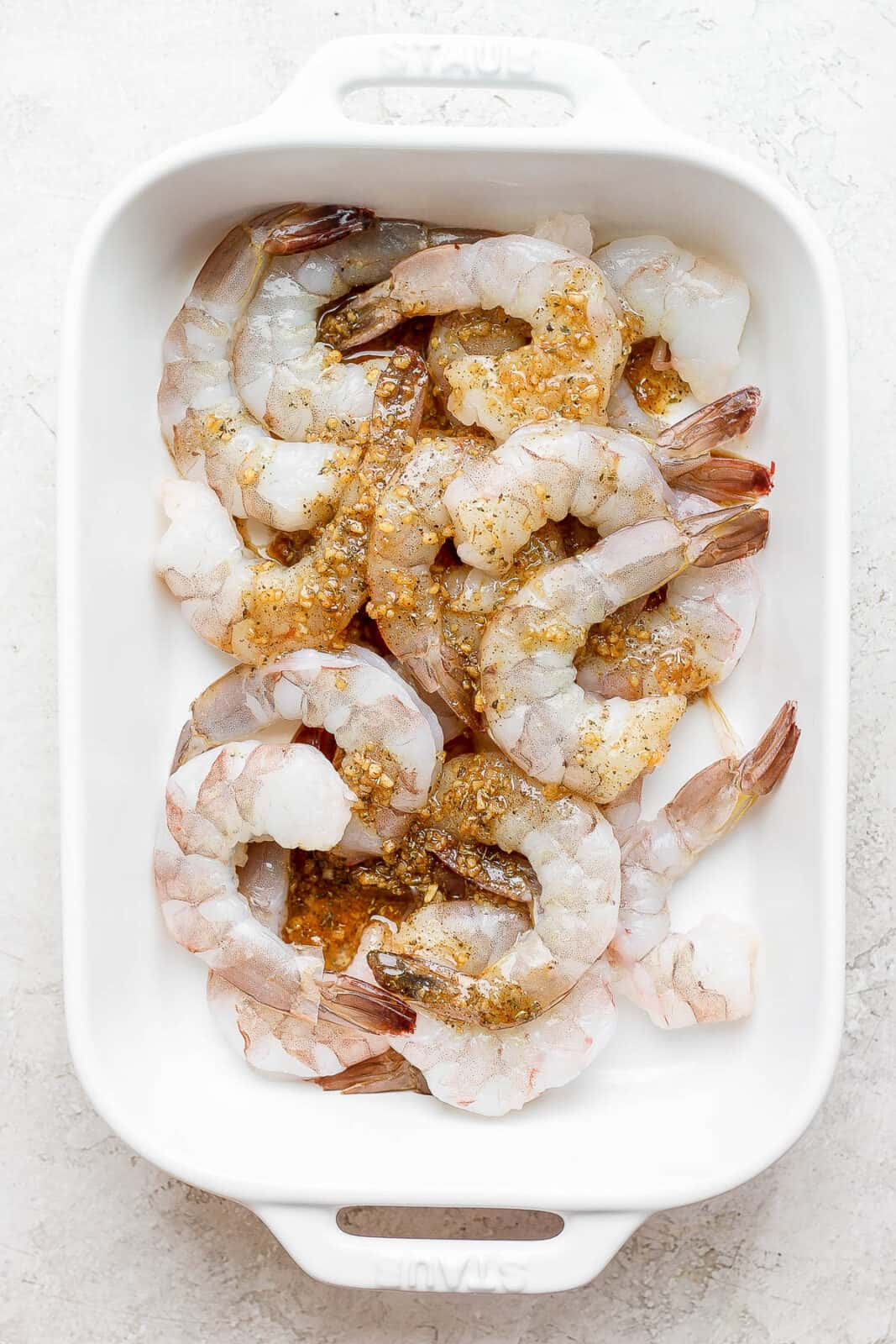 Shrimp in a pan with marinade on top.