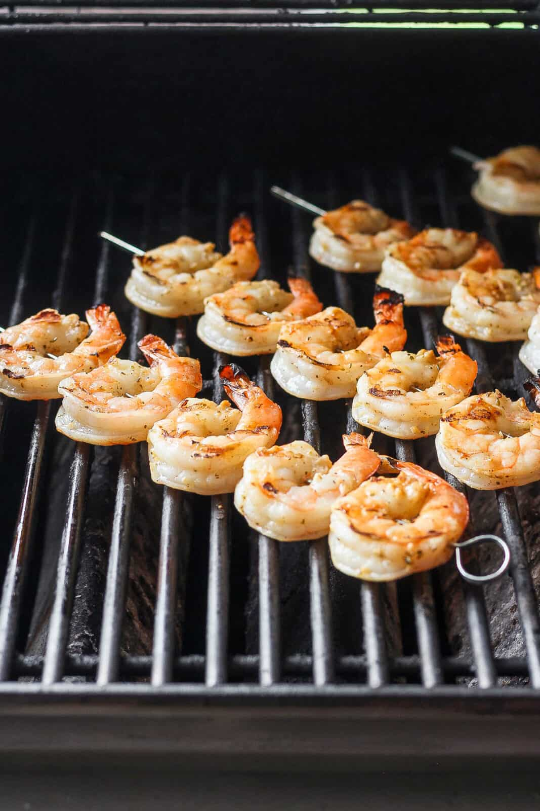 Marinated shrimp on skewers on the grill.