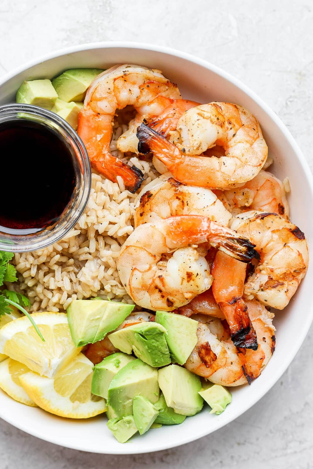 Pan fried shrimp in a bowl with rice, avocado, and a dish of soy sauce.