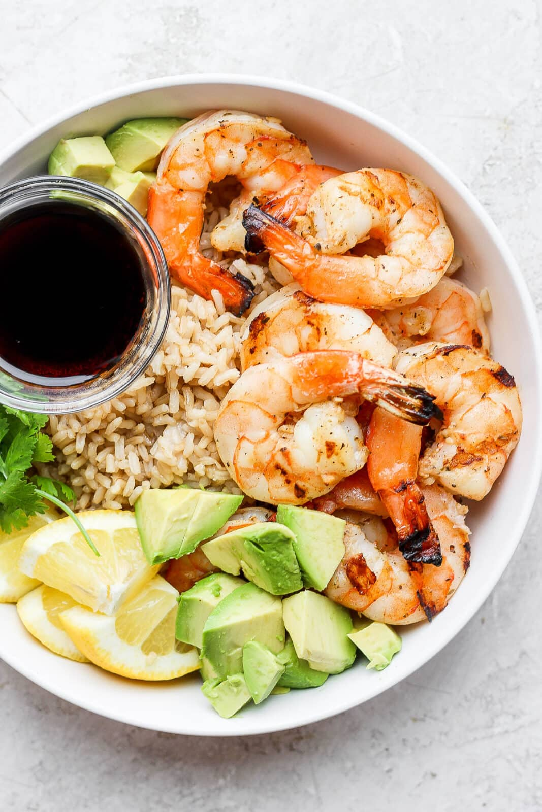 Shrimp rice bowl with a small dish of soy sauce.