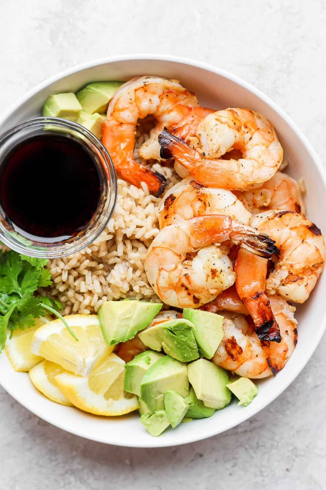 Shrimp rice bowl with a dish of soy sauce.