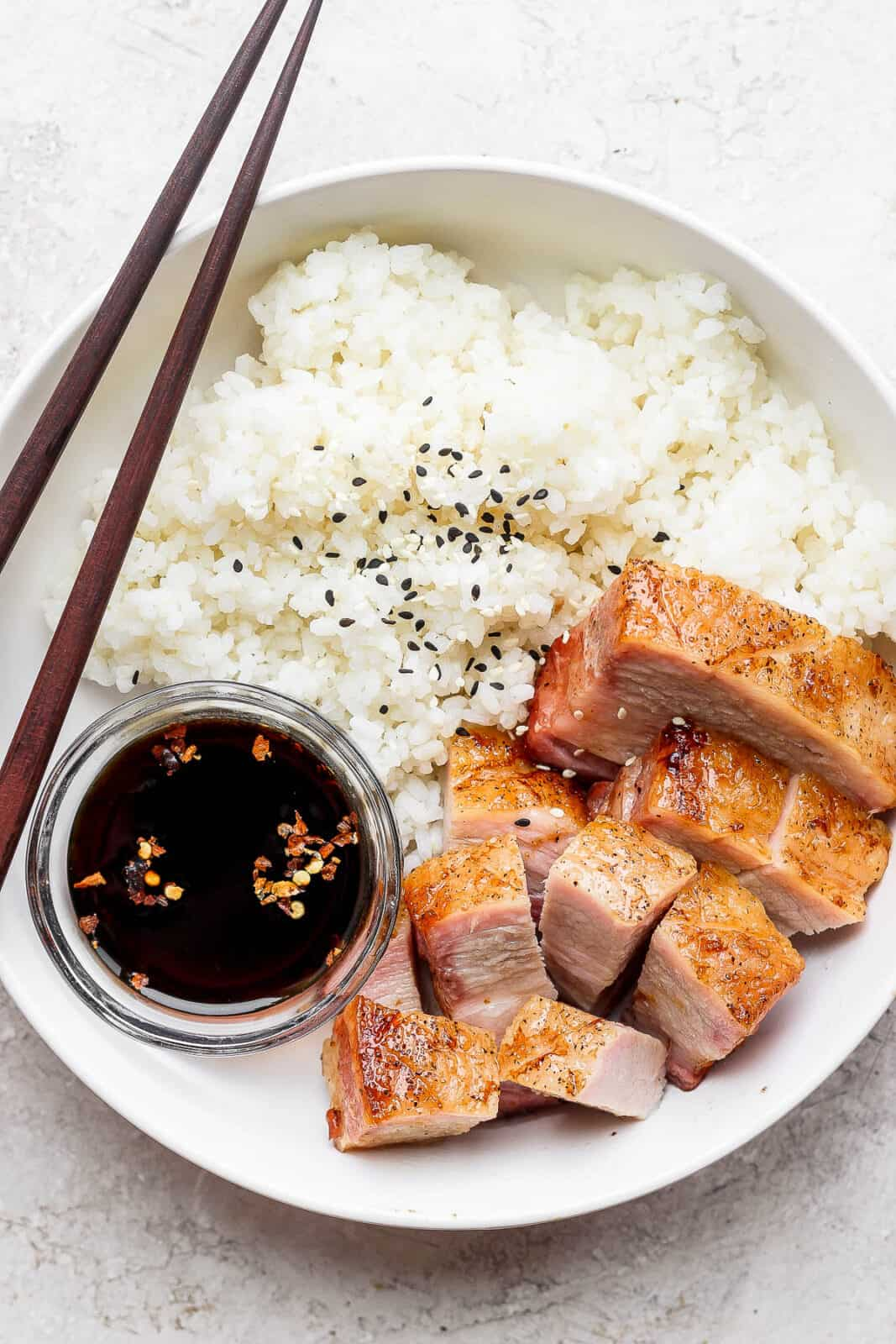 A bowl of rice, soy sauce and pork belly.