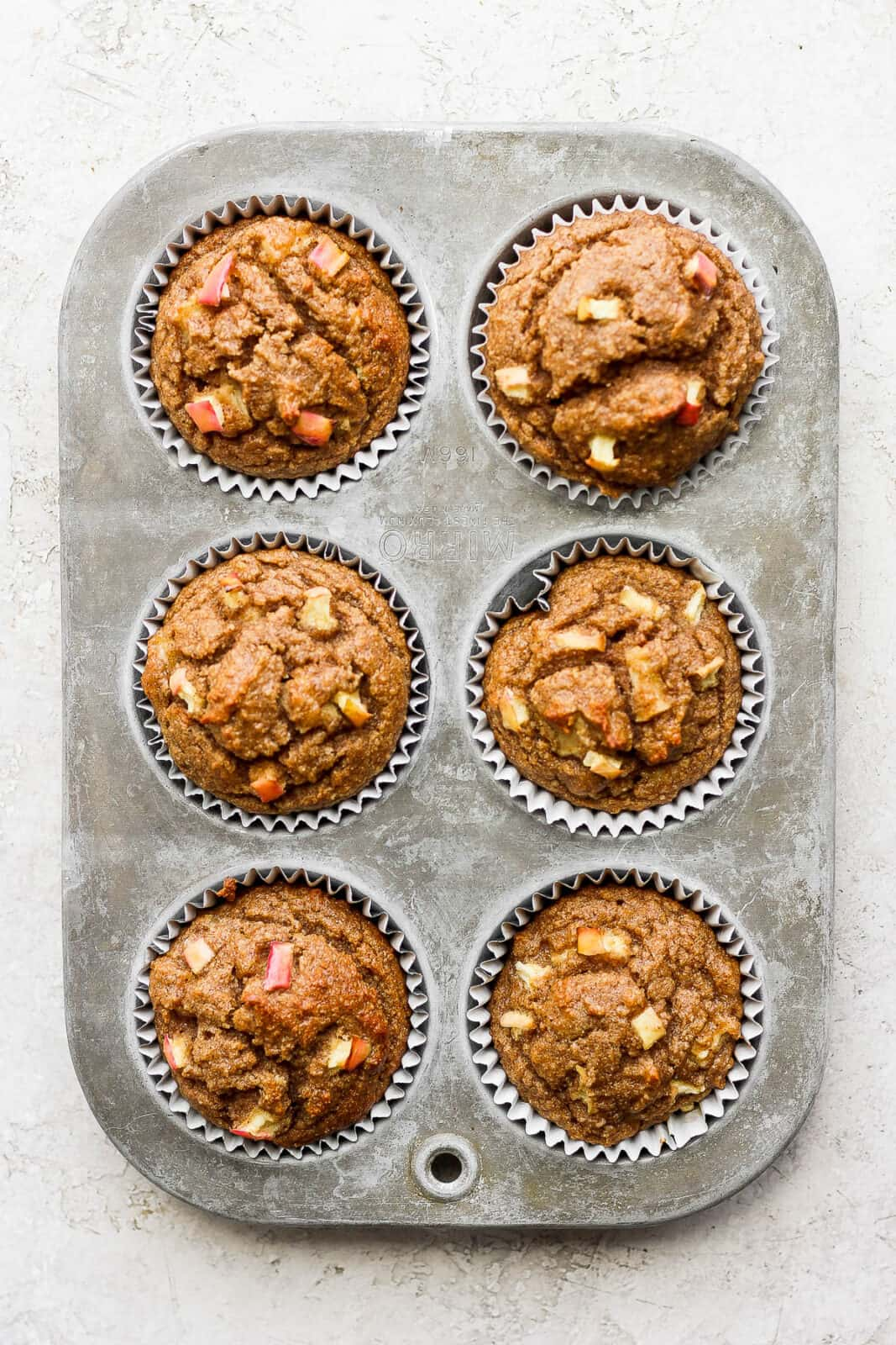 Apple cinnamon muffins in a muffin tin after baking.