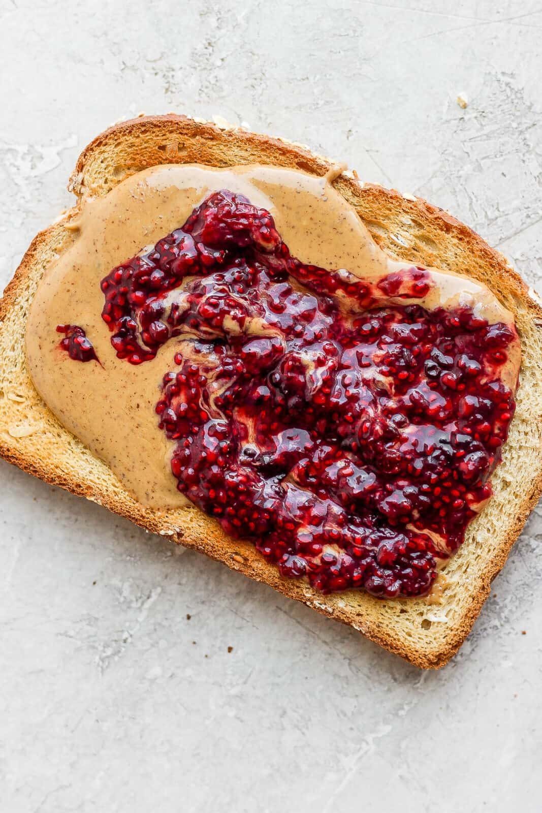 A piece of toast with almond butter and homemade chia sed jam spread on it.