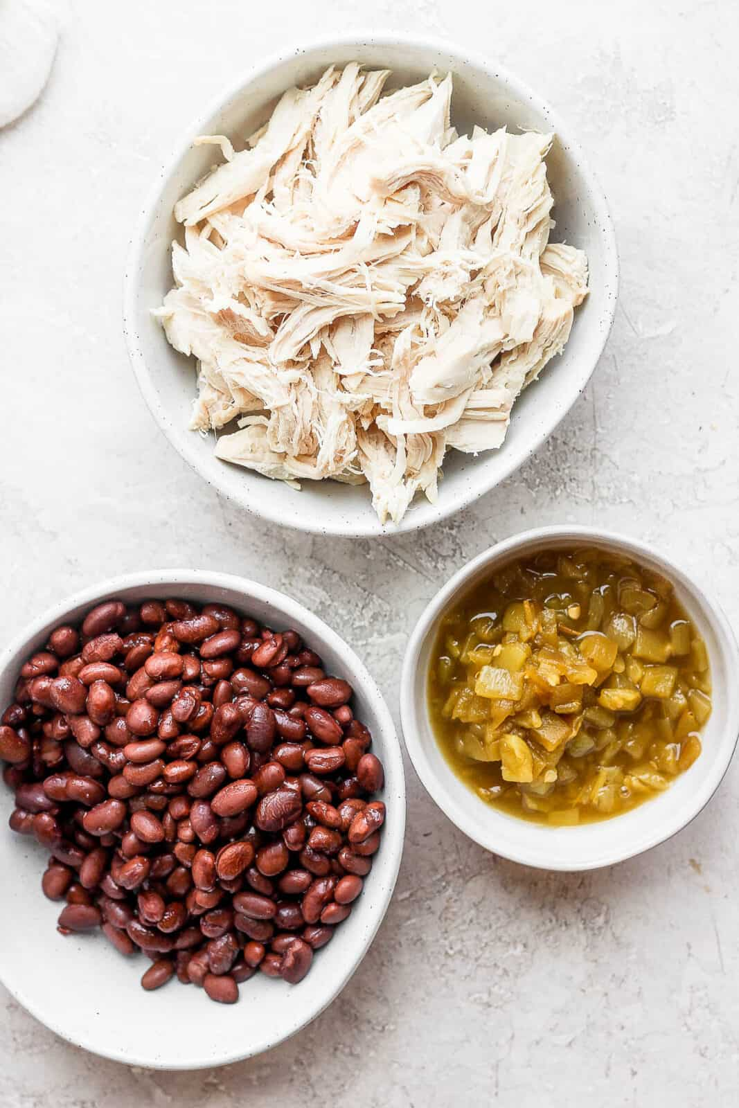 Three bowls with shredded chicken, green chiles and black beans in each.