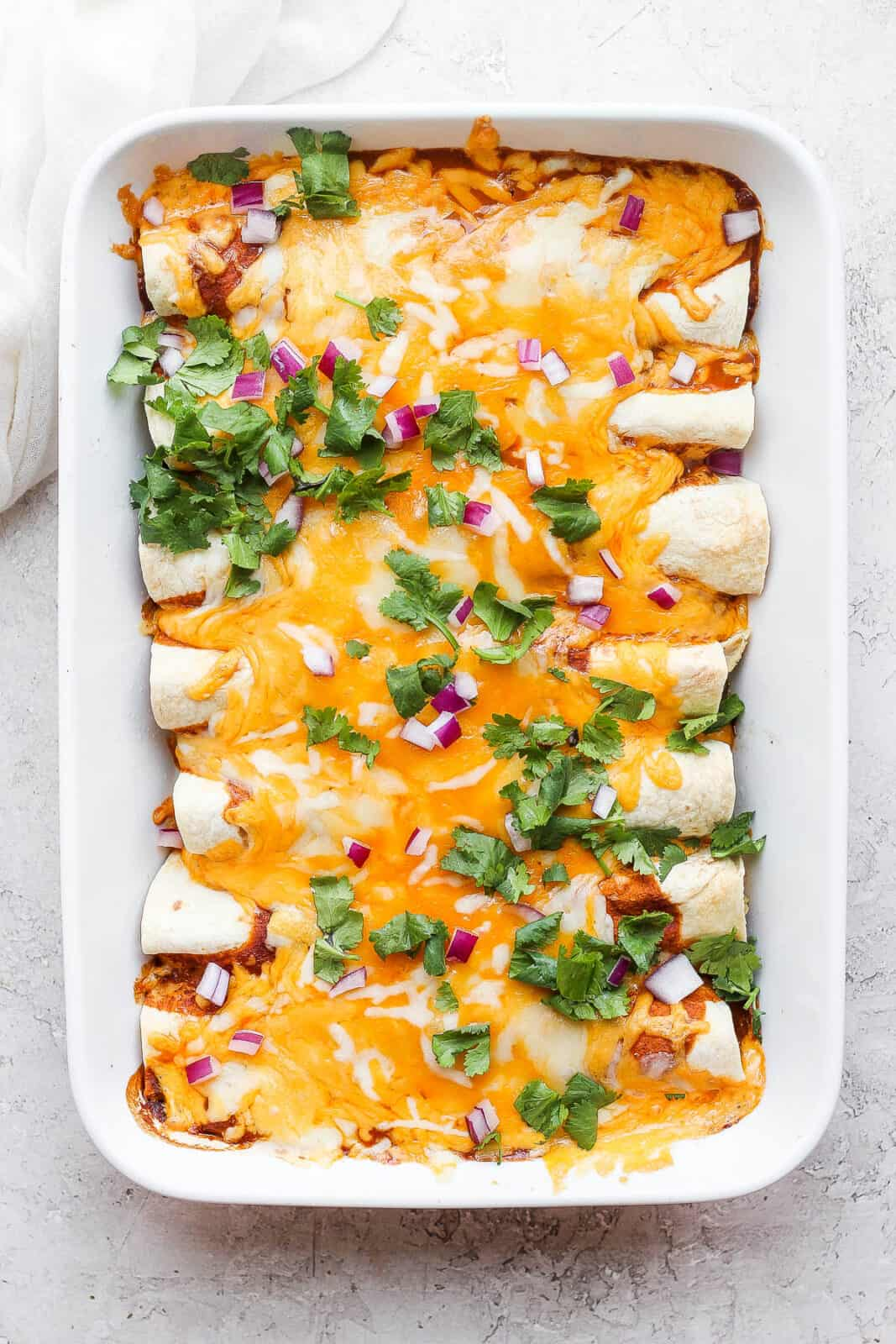 Chicken enchiladas in a baking dish.