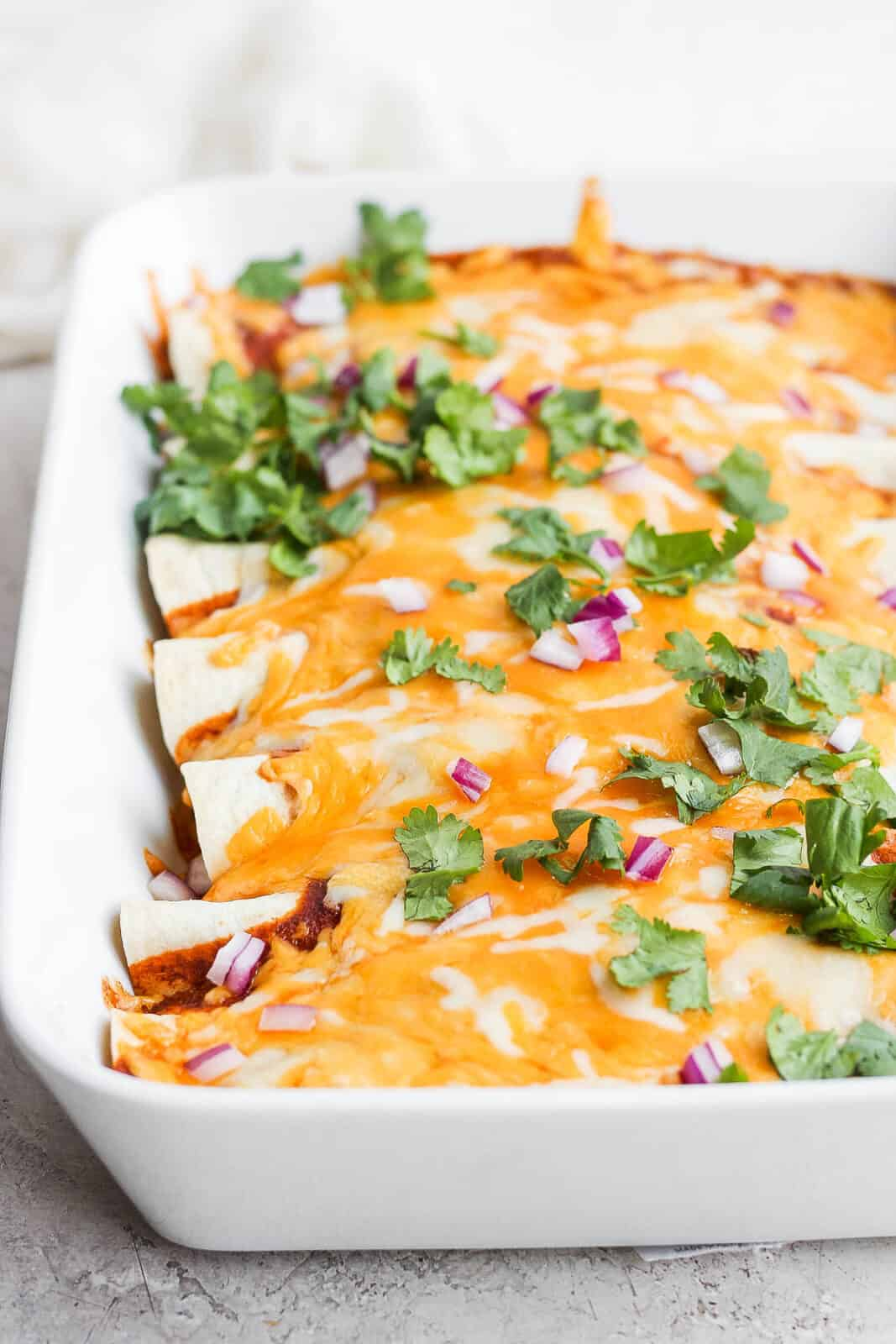 Side view of a pan of healthy chicken enchiladas.