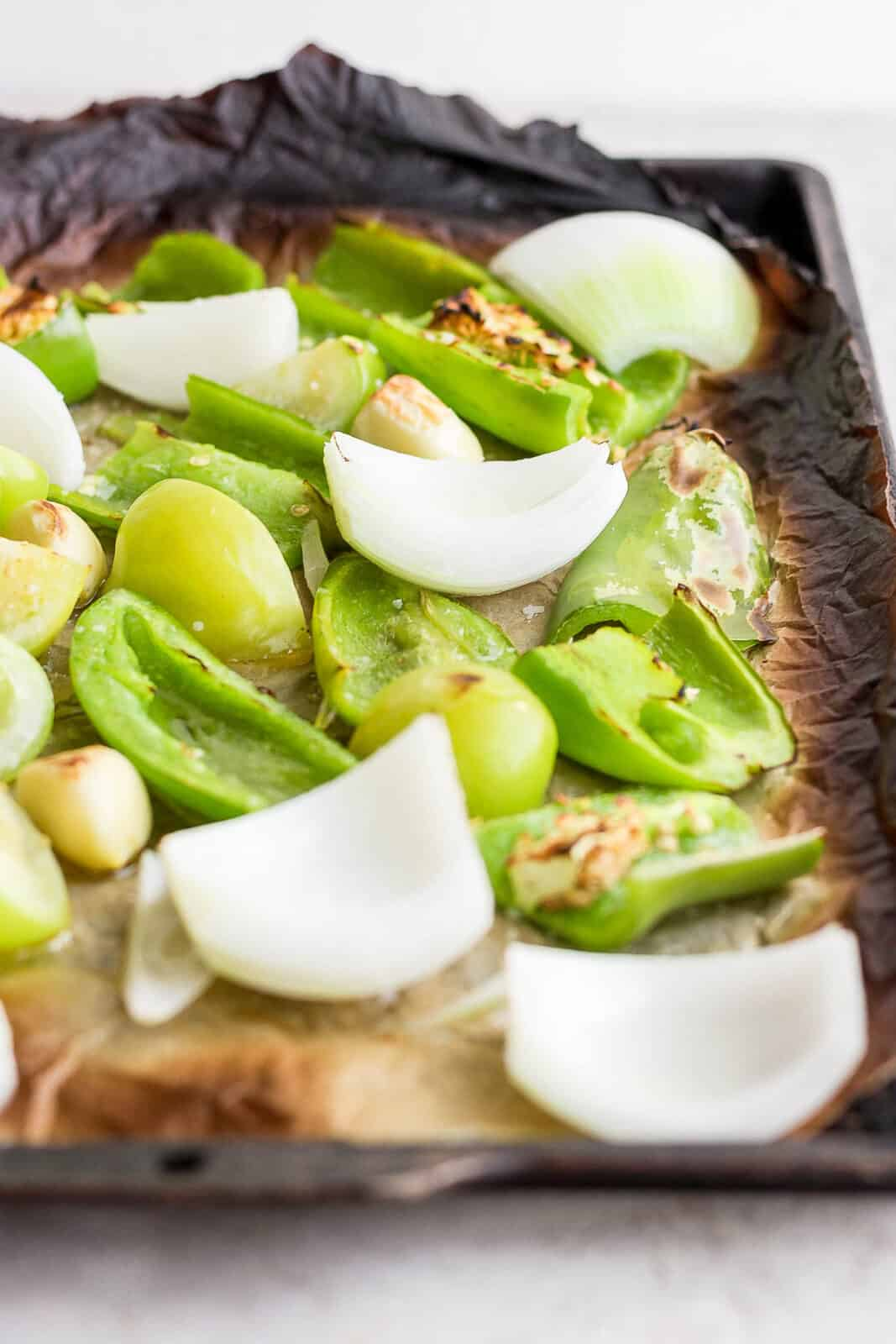 Roasted tomatillos, anaheim pepper, jalapeno, garlic, and onion on a parchment-lined pan.