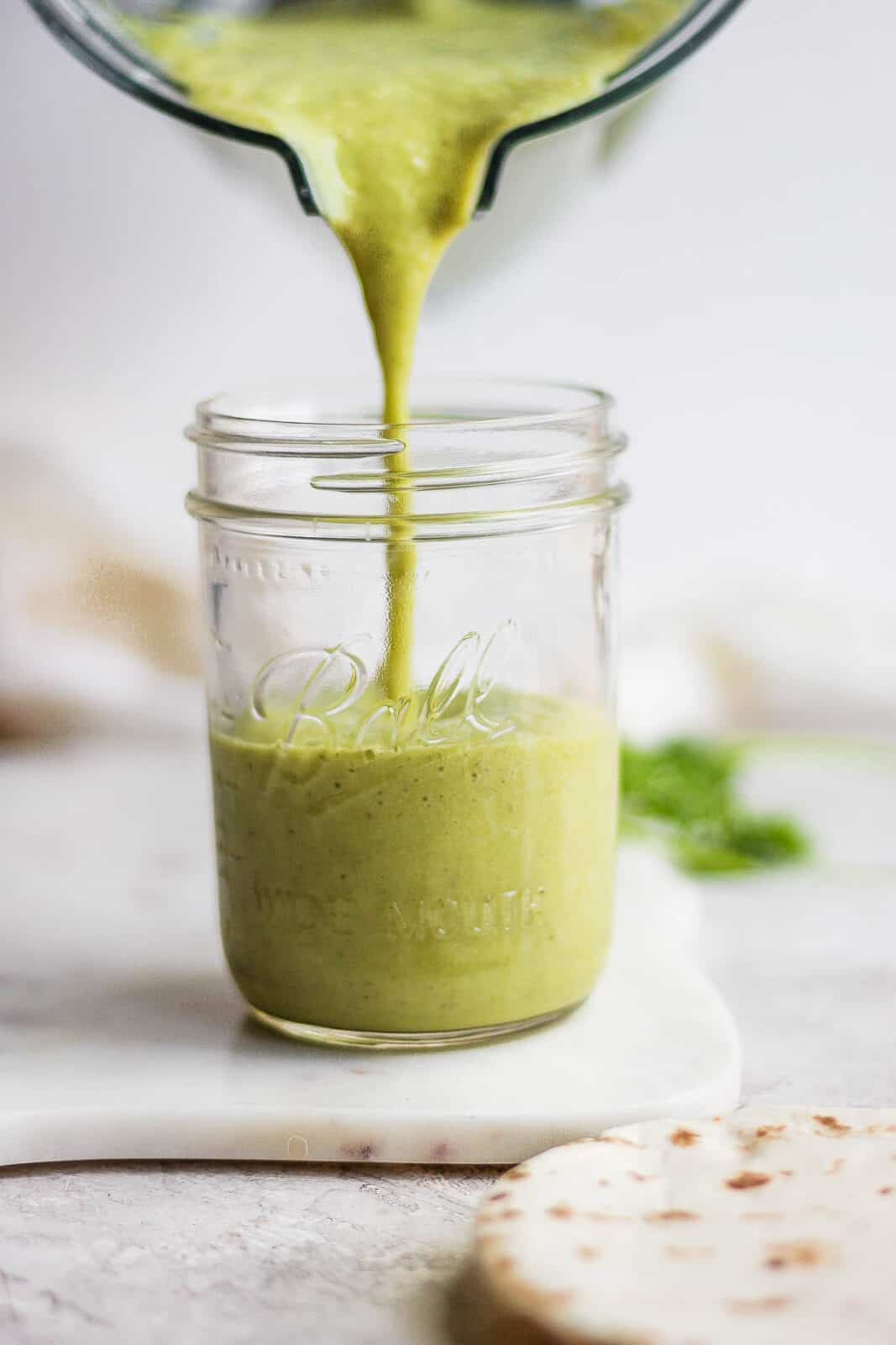 Green enchilada sauce being poured from a blender into a mason jar.