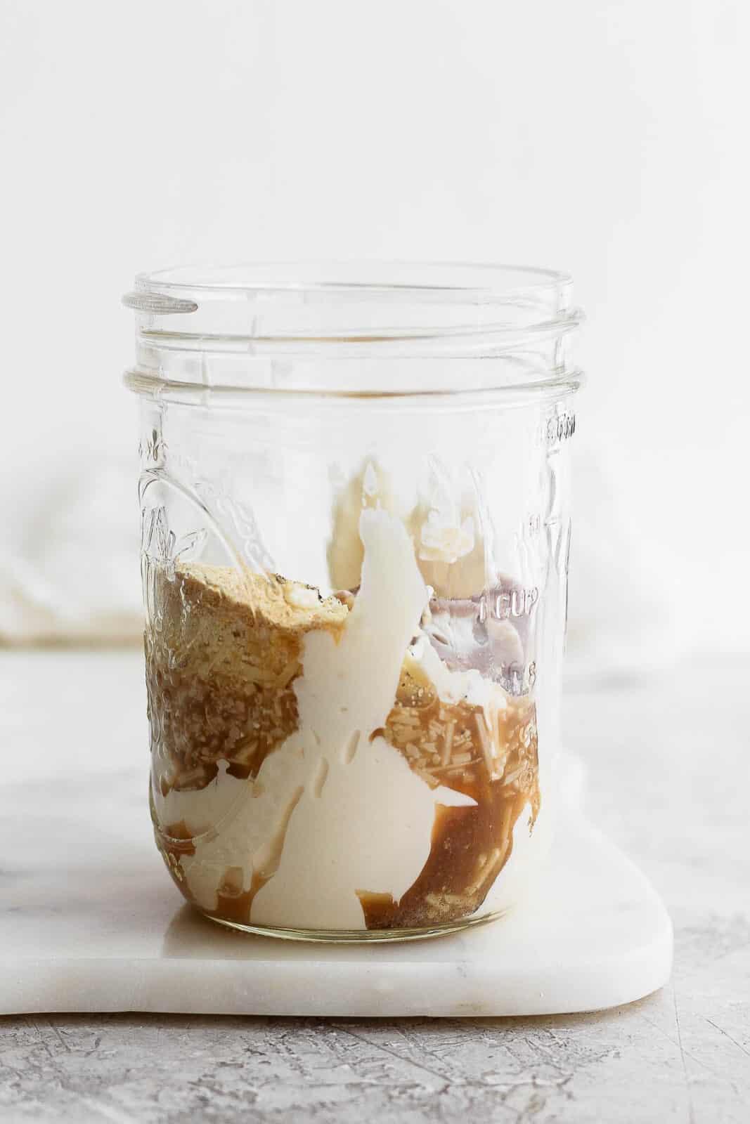 Healthy caesar dressing ingredients in a mason jar.