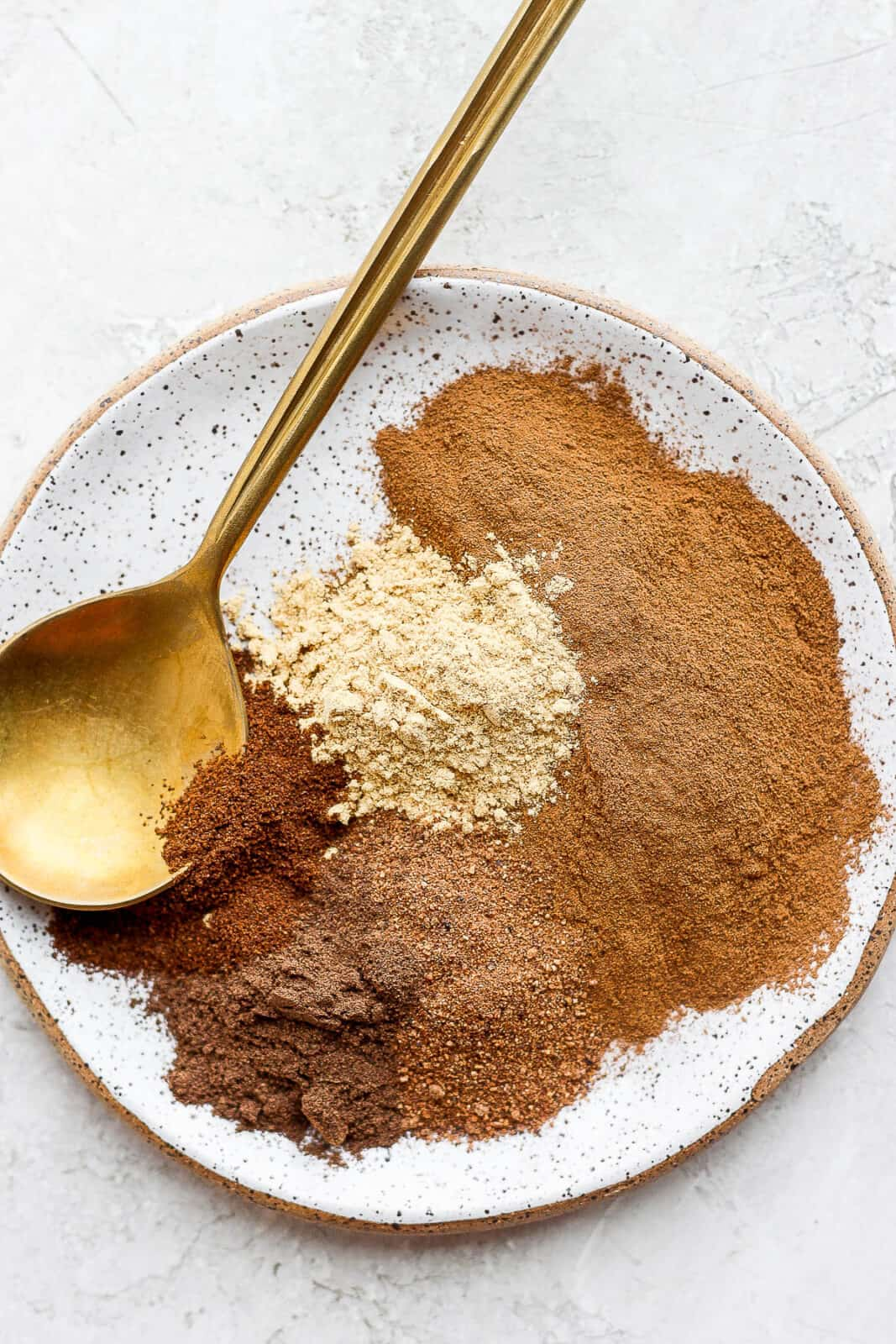 Pumpkin spice ingredients on a plate with a spoon.
