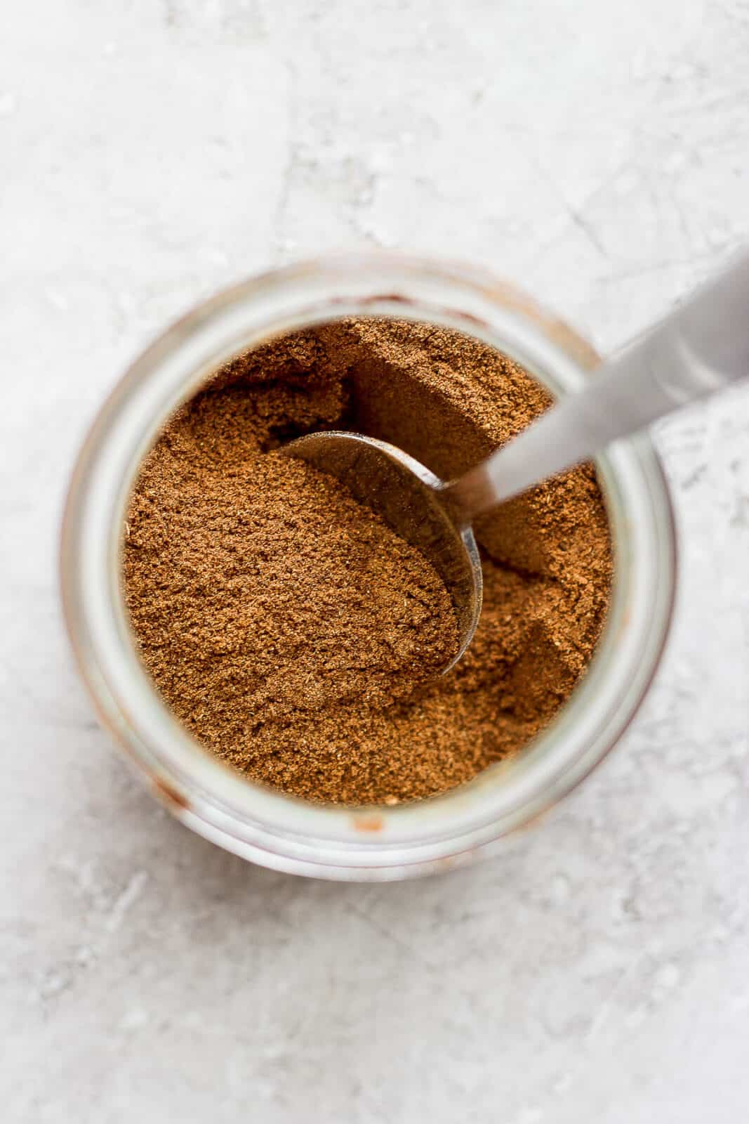 Pumpkin spice ingredients mixed together in a jar with a spoon.