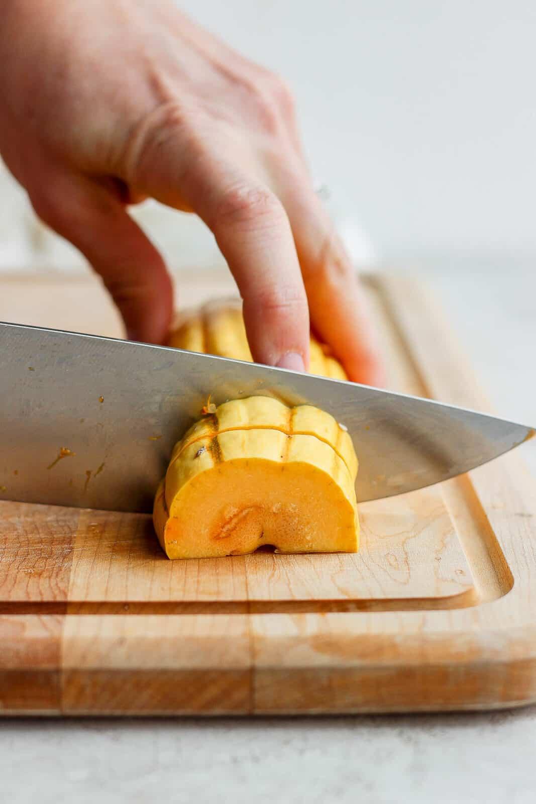 A delicata squash being cut into slices.