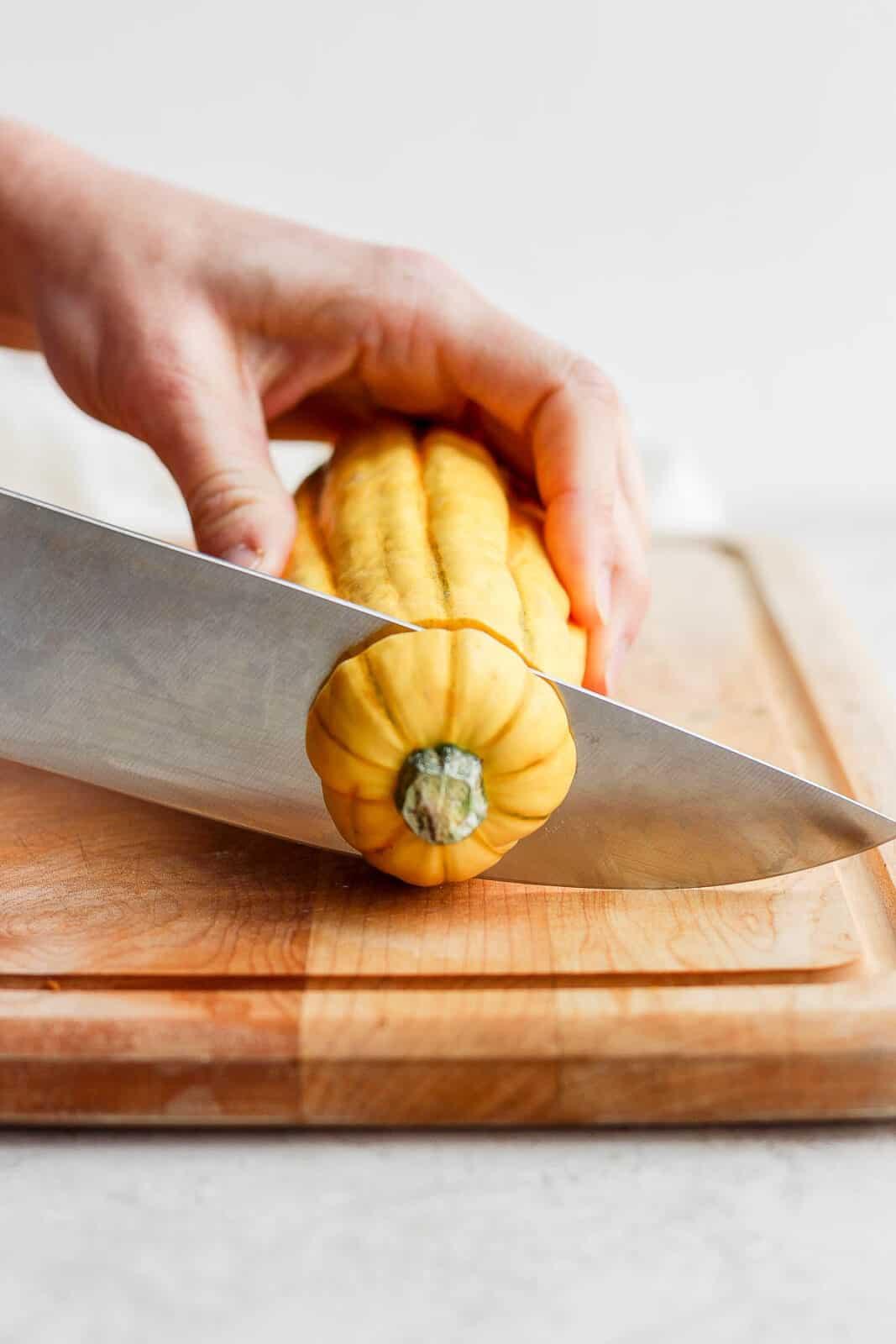 A knife cutting the top off a delicata squash.