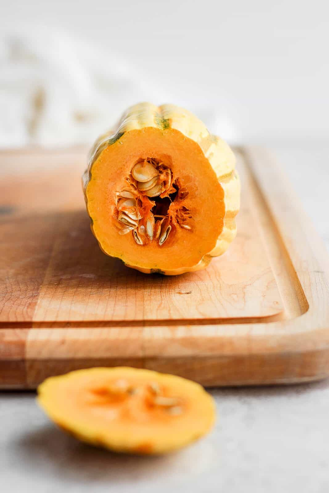 A delicata squash on a cutting board with the end cut off.