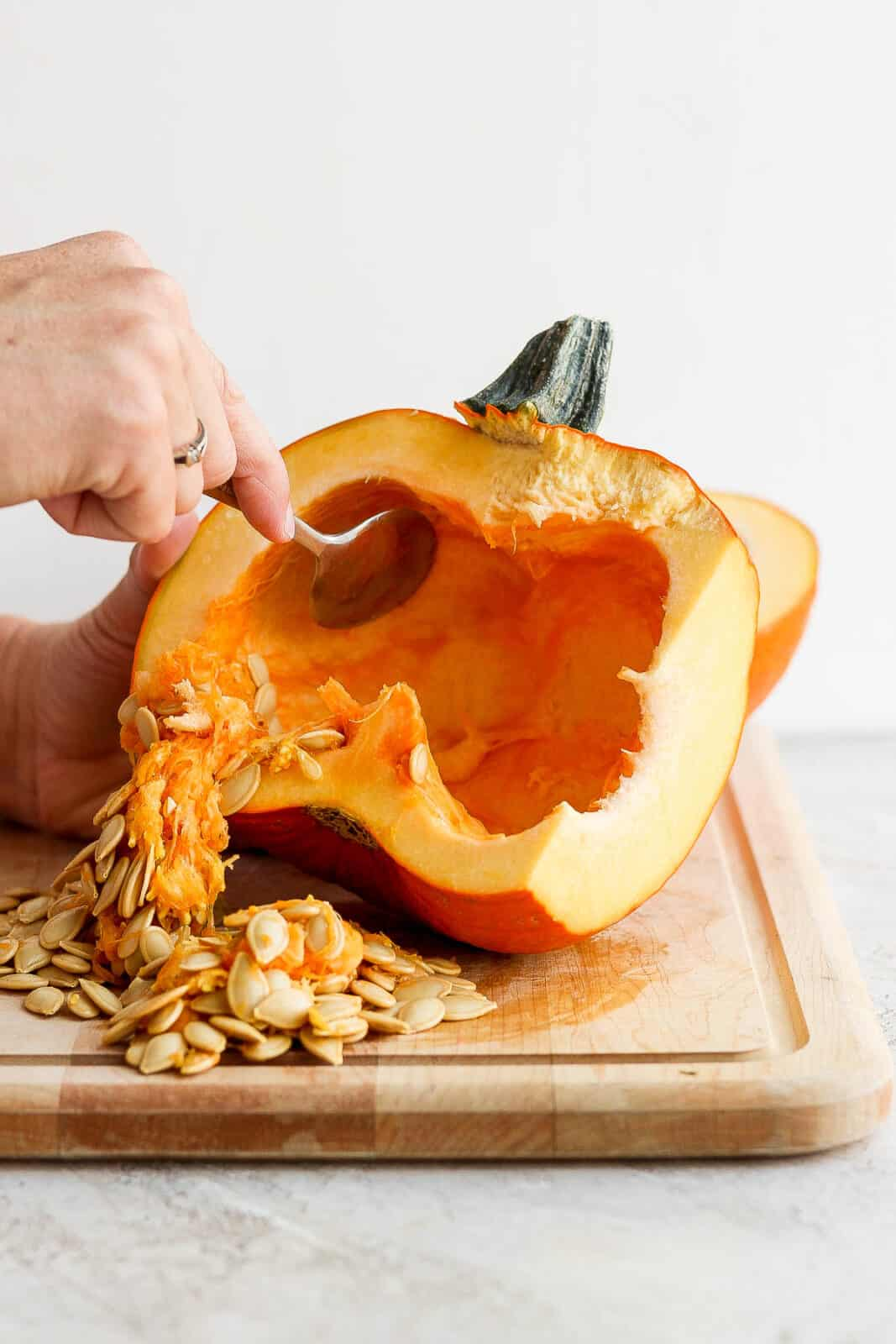A spoon scooping the seeds and strings out of the pumpkin.