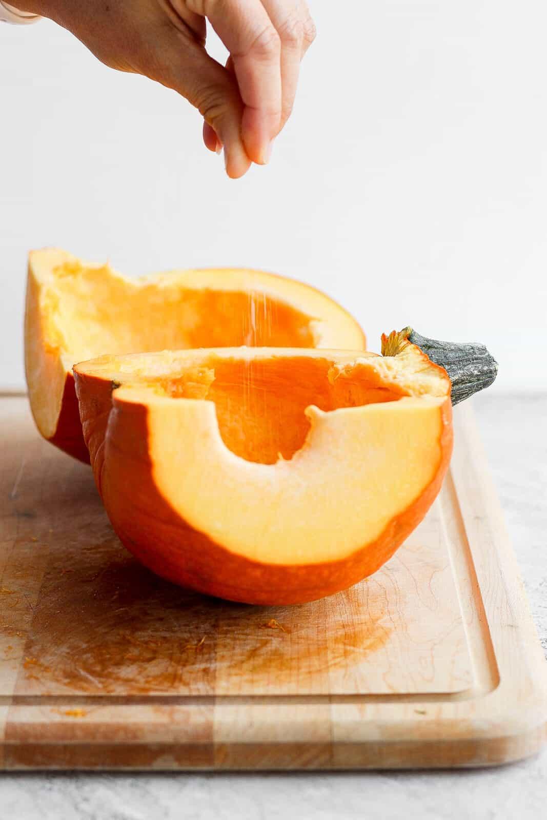 Sprinkling kosher salt on the two pumpkin halves.