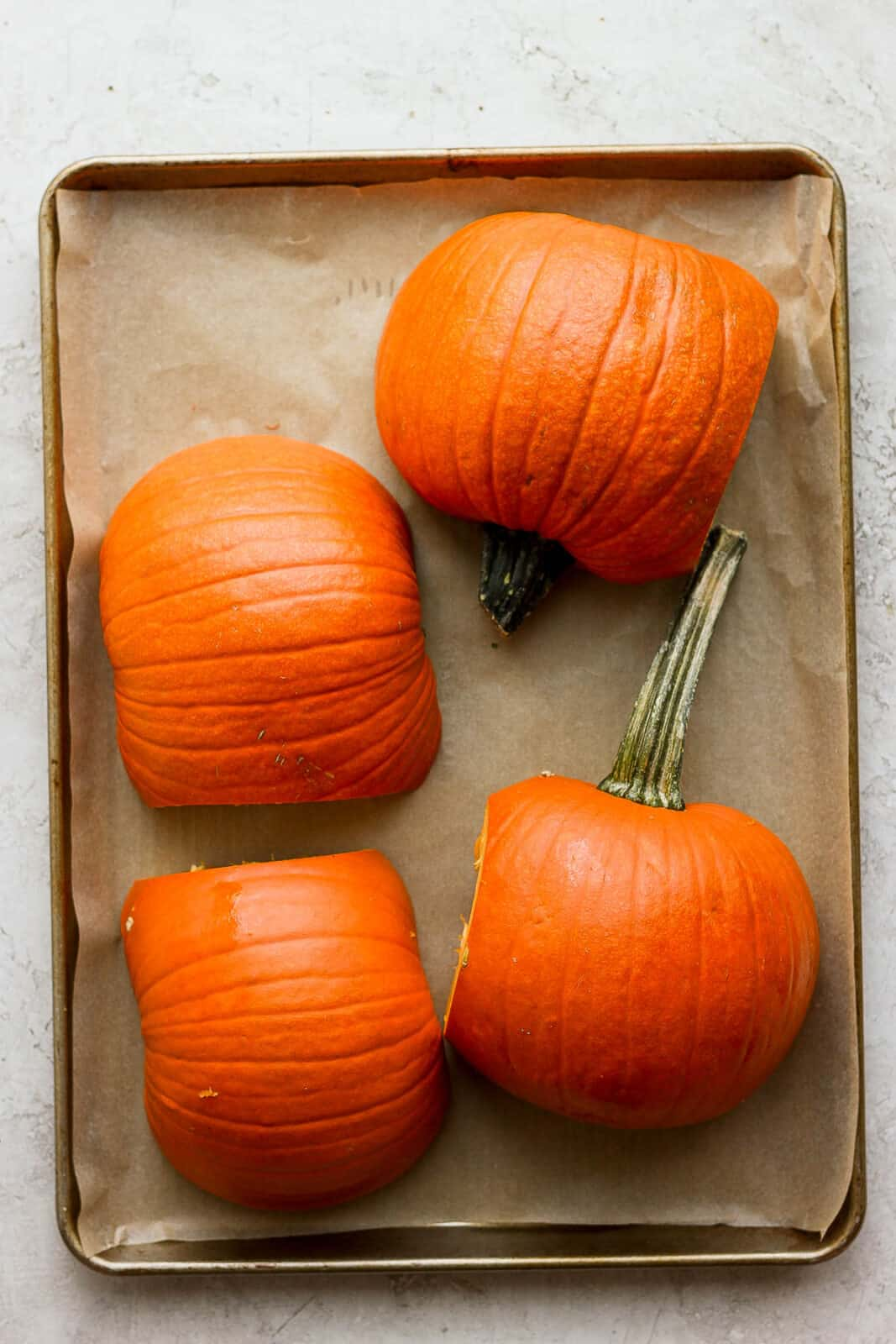 Pumpkin halves placed cut-side down on a parchment-lined baking sheet.