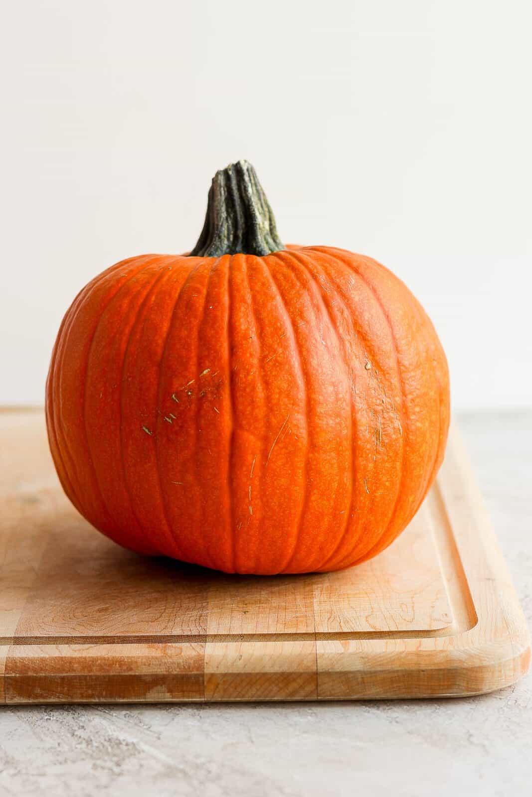 A small, baking pumpkin on a cutting board.