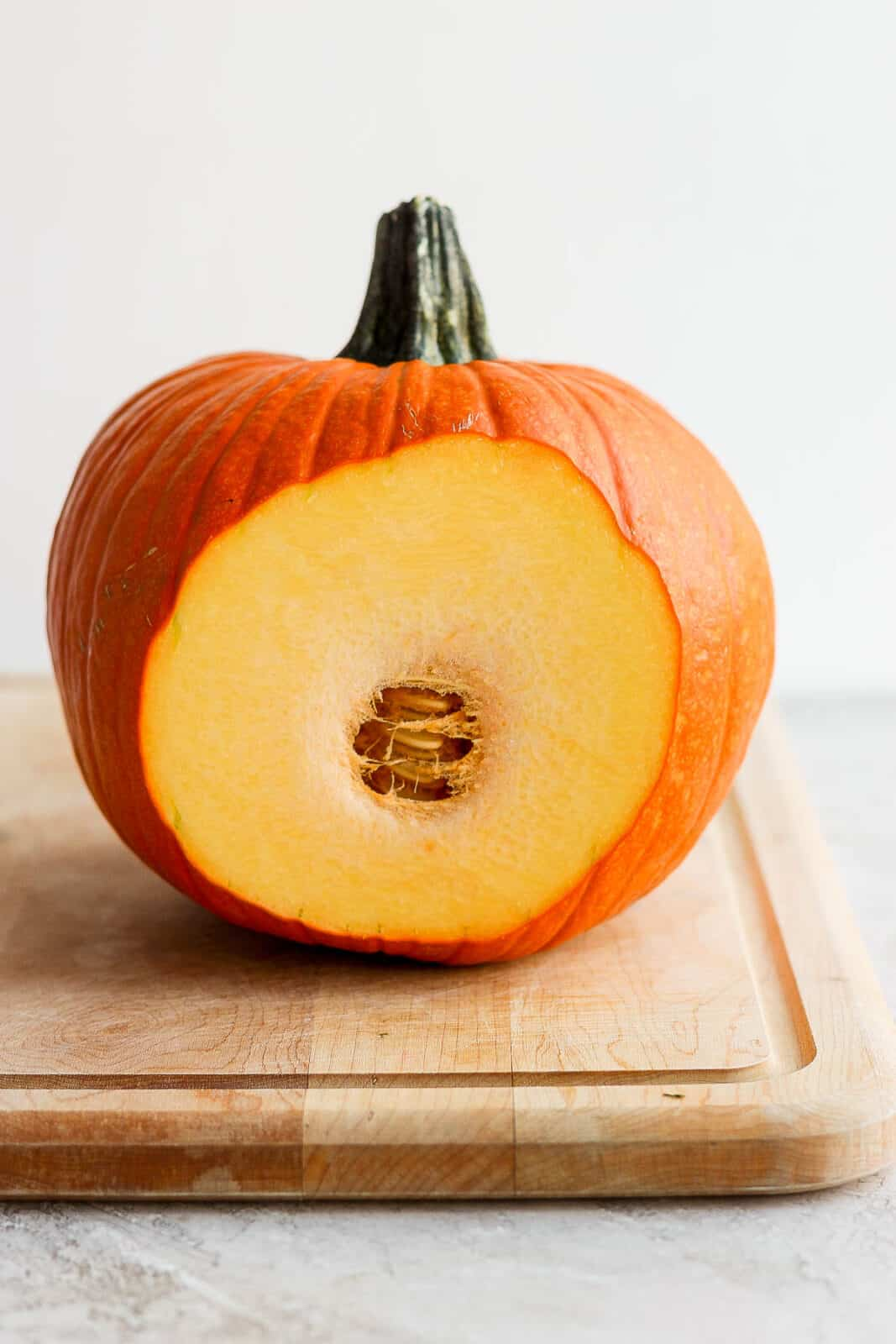 A pumpkin with a thin slice cut off the side.