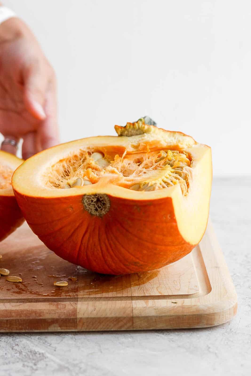 Half of a small, baking pumpkin on a cutting board.