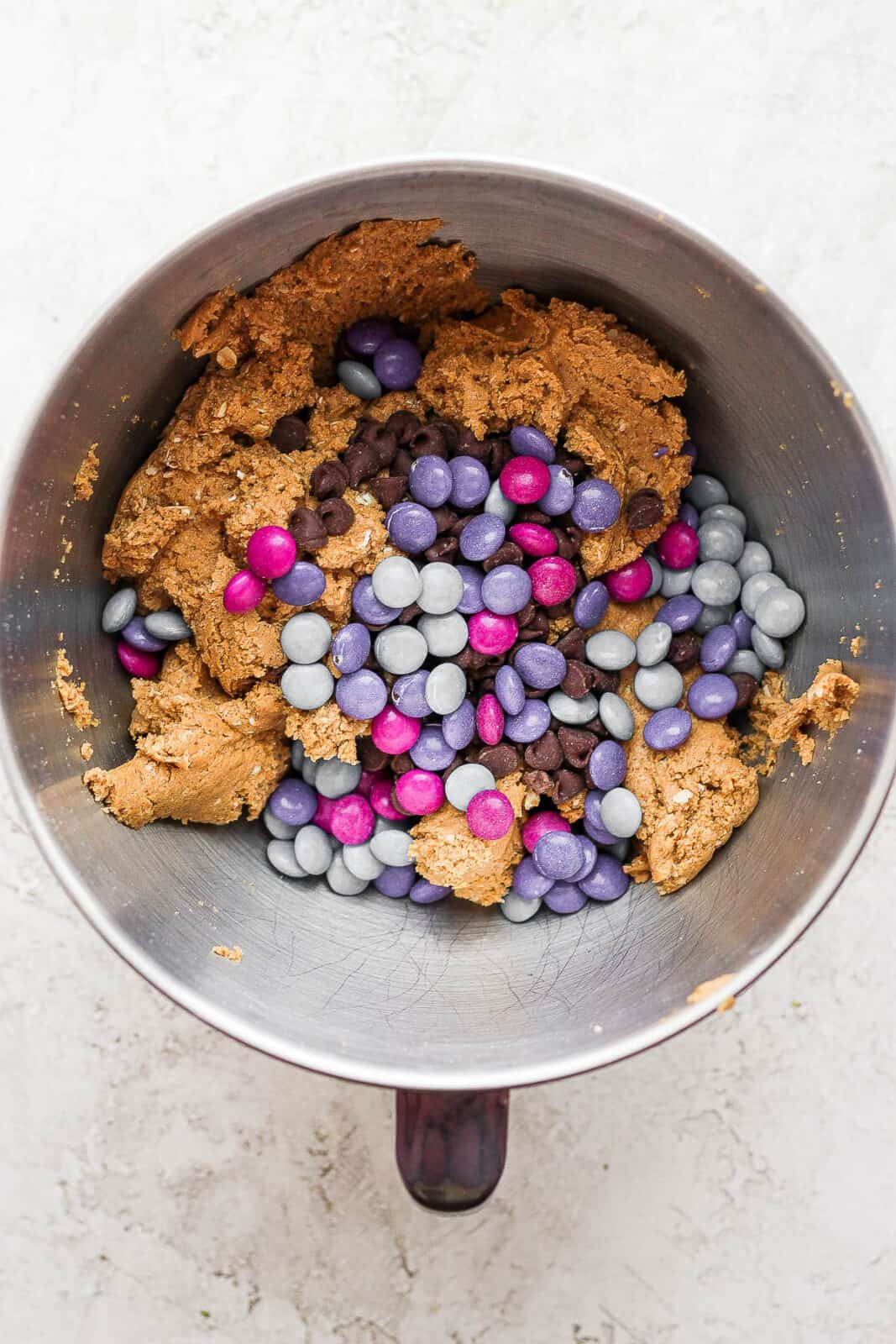 Monster cookie dough in a bowl with chocolate chips and m&ms.