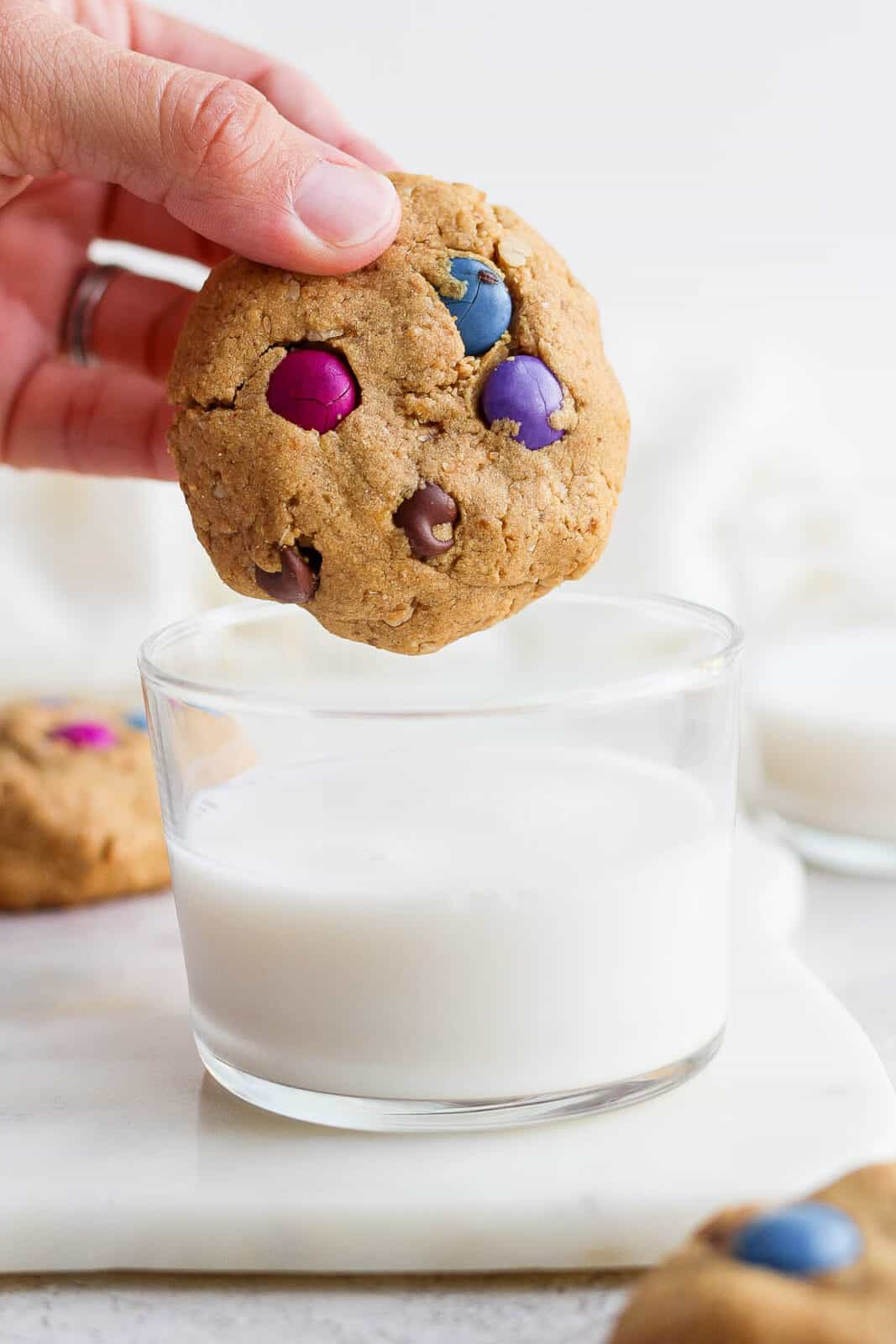 Someone about to dip a monster cookie in a cup of milk.